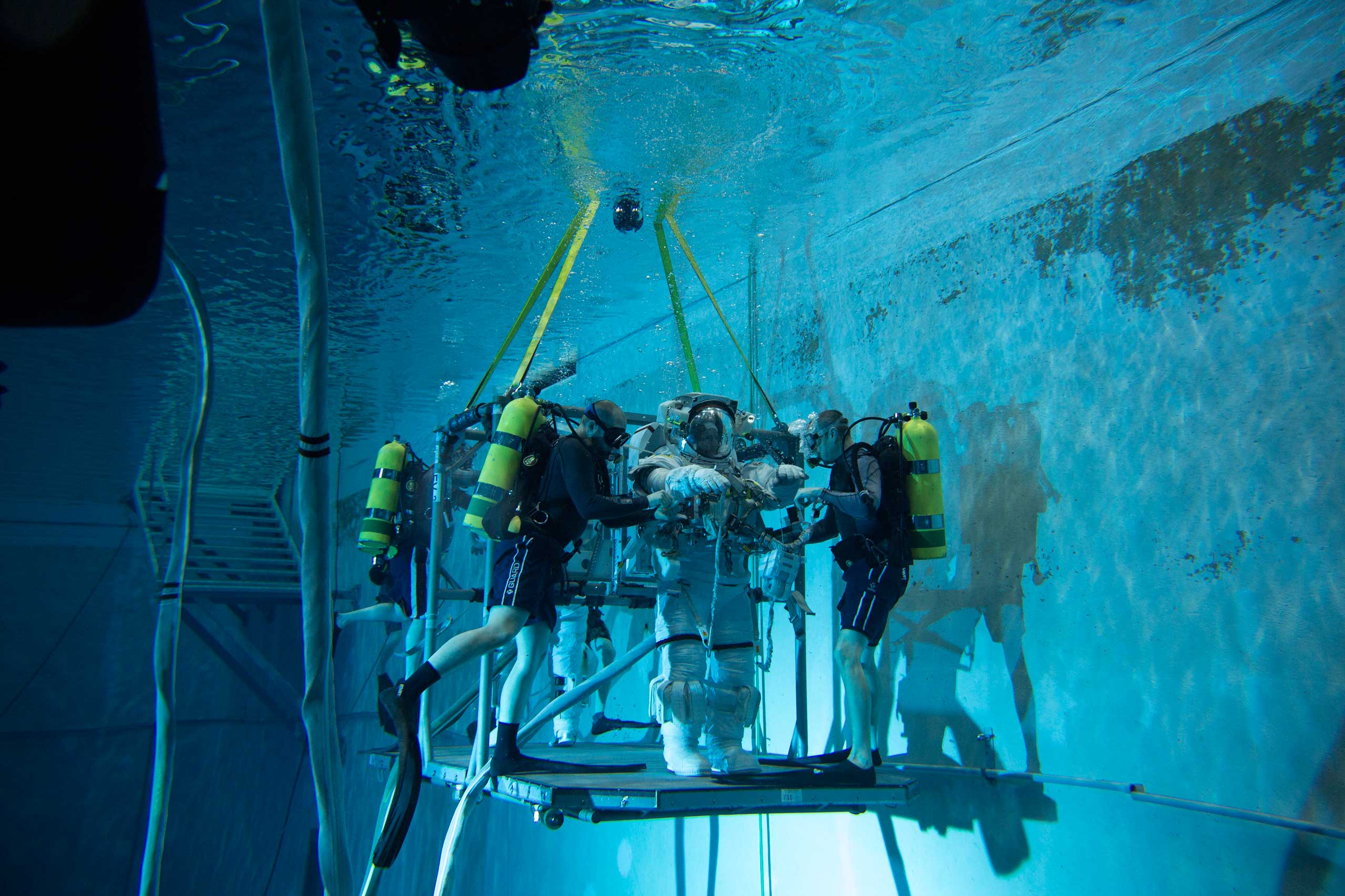 Divers check Scott Kelly's suit for leaks as he prepares for underwater training on in Houston on Feb. 2. Even though the spacesuit, which have been modified for use in the pool, weighs more than Scott, due to the air inside it, he does not sink like a rock in the pool, but instead becomes neutrally buoyant, simulating weightlessness.