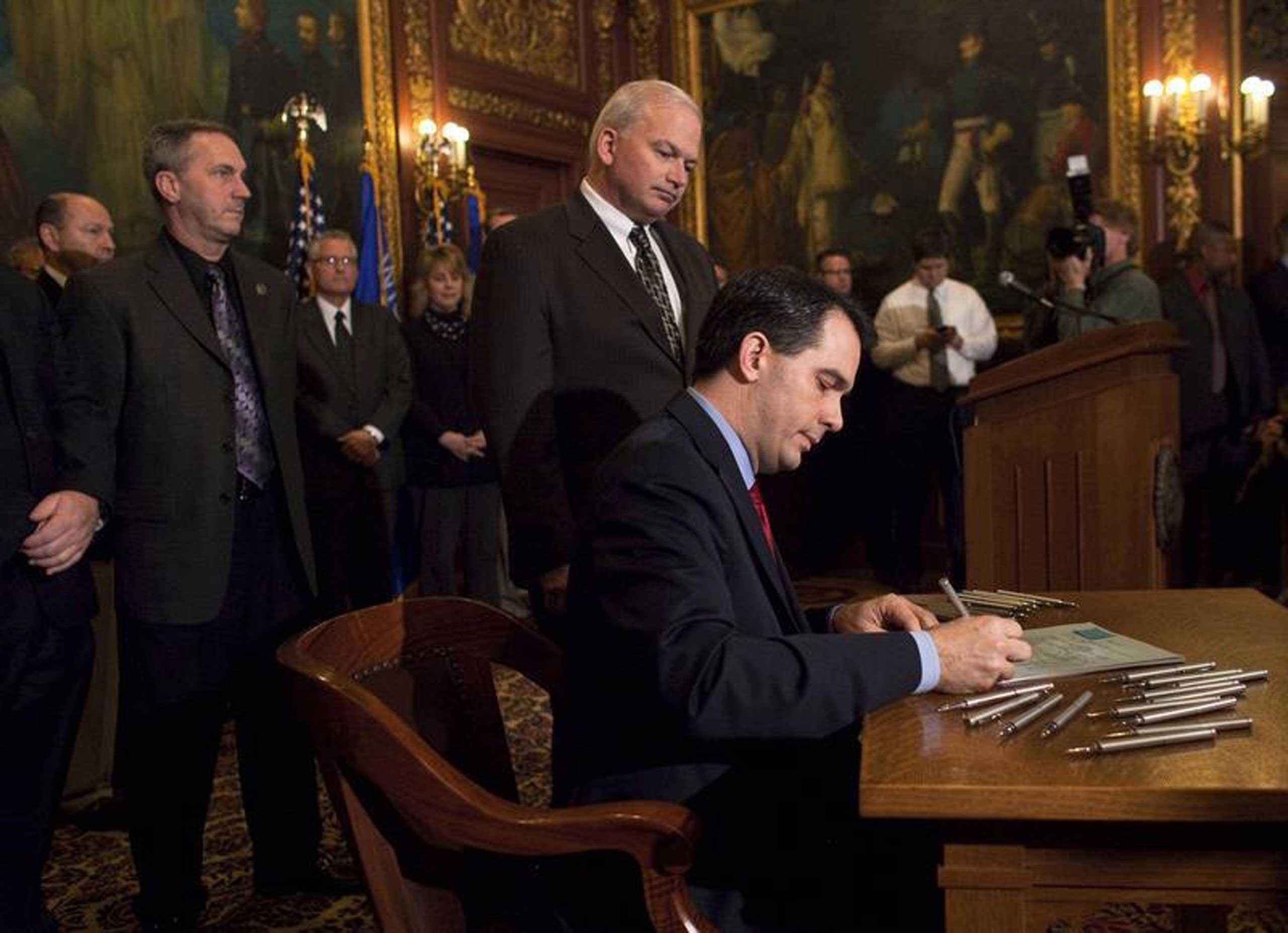 Wisconsin State Governor Scott Walker signs the ceremonial bill, after the Republican-controlled House and Senate eliminated almost all collective bargaining for most public workers at the state Capitol in Madison Wis., March 11, 2011.