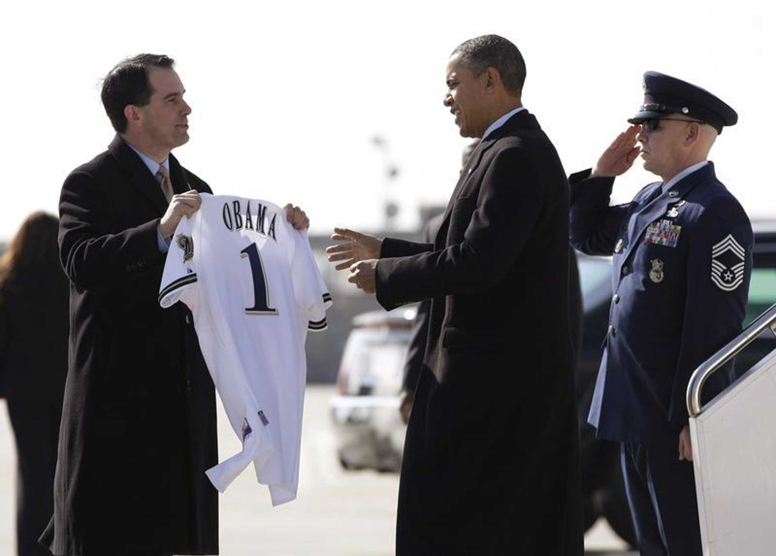 Wisconsin Governor Scott Walker presents U.S. President Barack Obama with a Milwaukee Brewers jersey upon his arrival in Milwaukee, Wis., on Feb. 15, 2012.