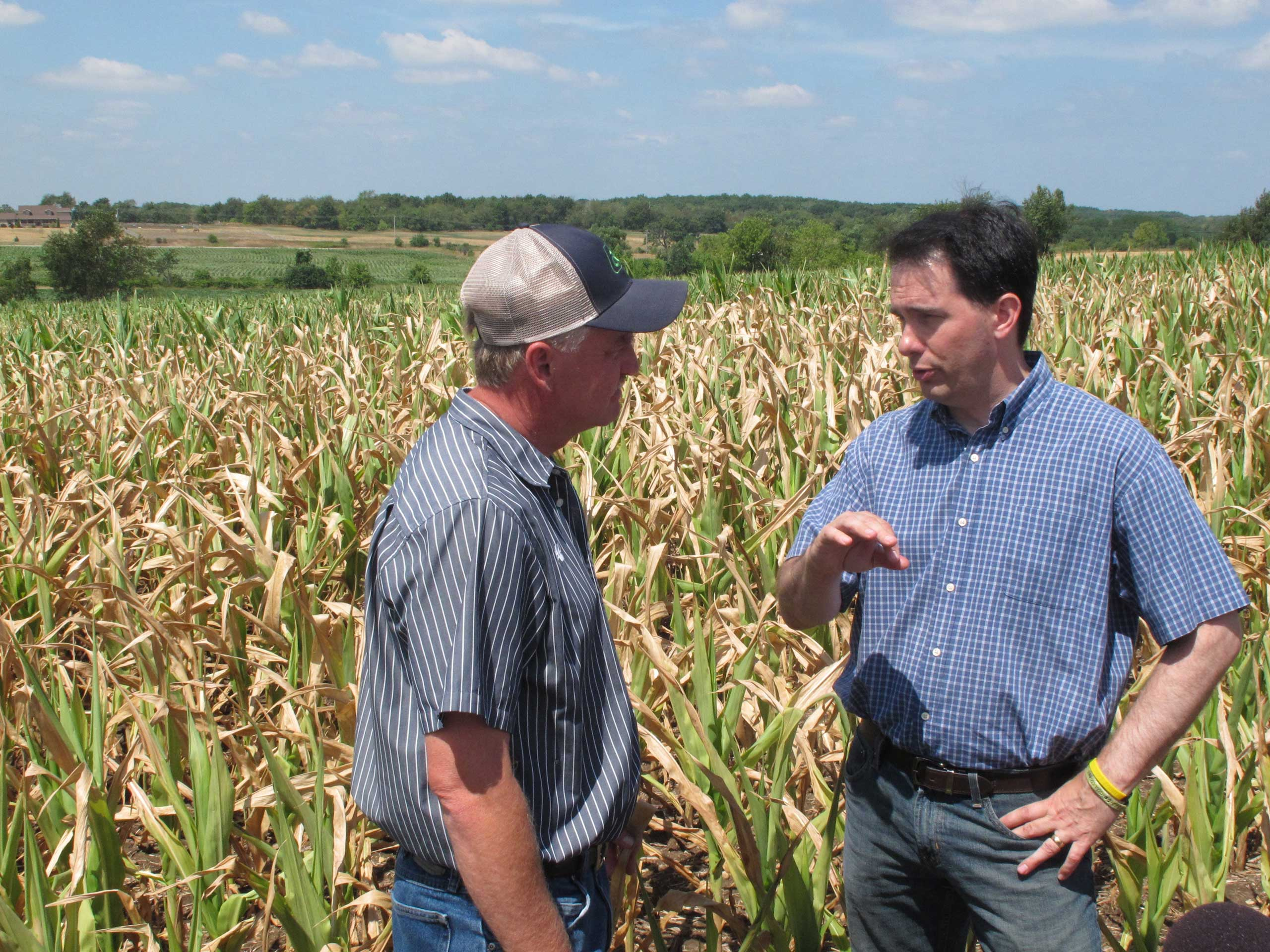Gov. Scott Walker, right, talks with farmer Jeff Ehrhart about drought damage to his corn crop in the background in Burlington, Wis., on July 20, 2012.