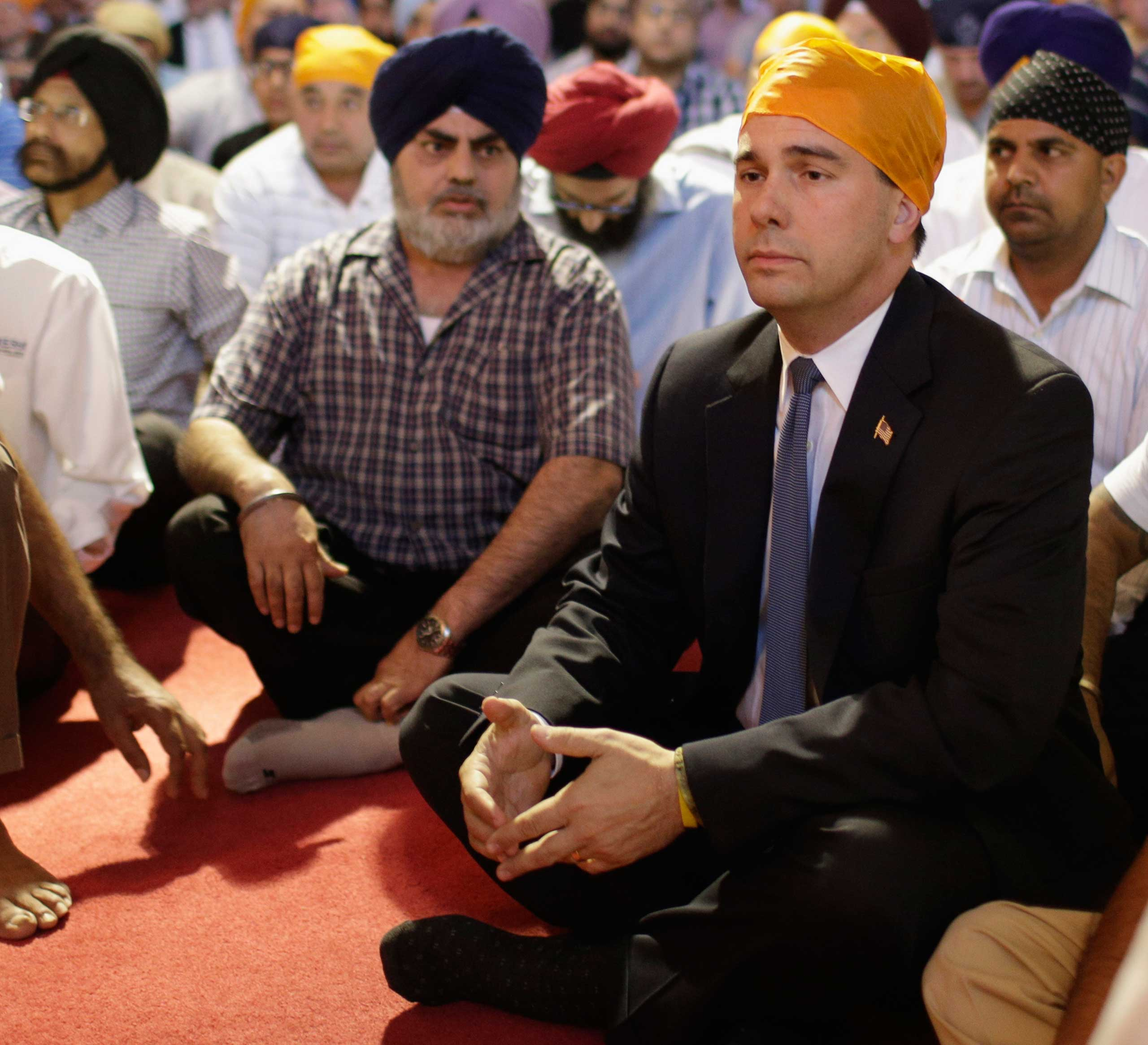 Wisconsin Governor Scott Walker attends a prayer service at the Sikh Temple in Brookfield, Wis., on August 6, 2012.
