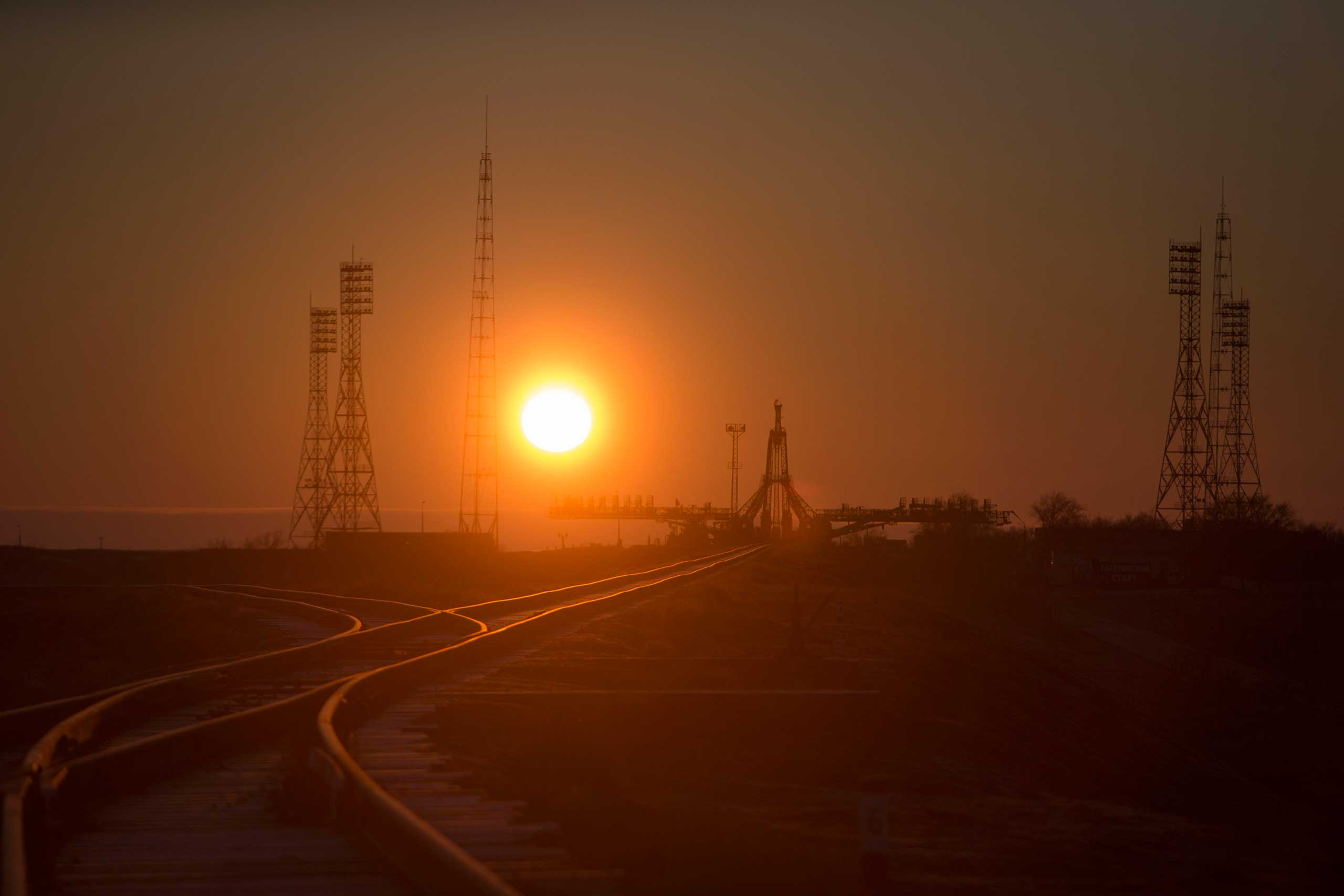 The sunrise silhouettes the structure that helps stabilize and service the Soyuz at the Baikonur Cosmodrome in Kazakhstan on Wednesday, March 25.