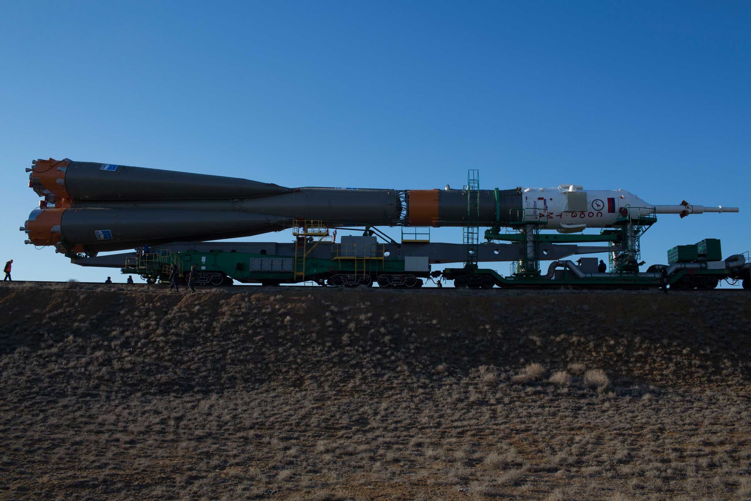 Roscosmos and guard service officials are dwarfed by the Soyuz rocket as it approaches Pad 1 at the Baikonur Cosmodrome in Kazakhstan on Wednesday, March 25.
