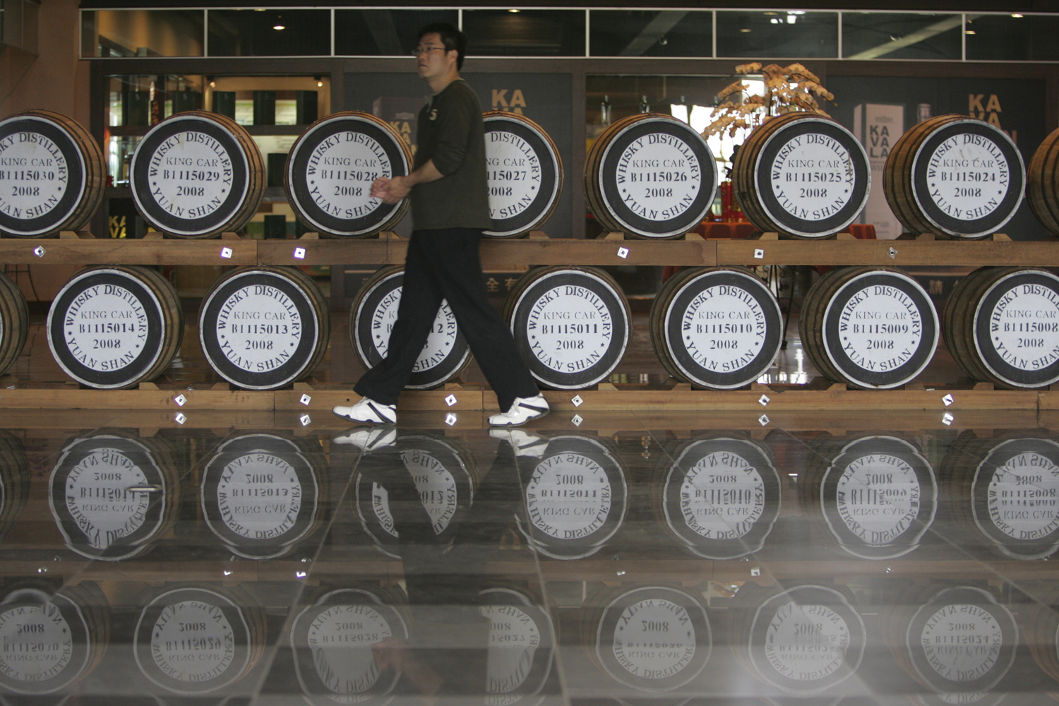A visitor walks past casks at the Kavalan whiskey distillery in Yilan County, Taiwan