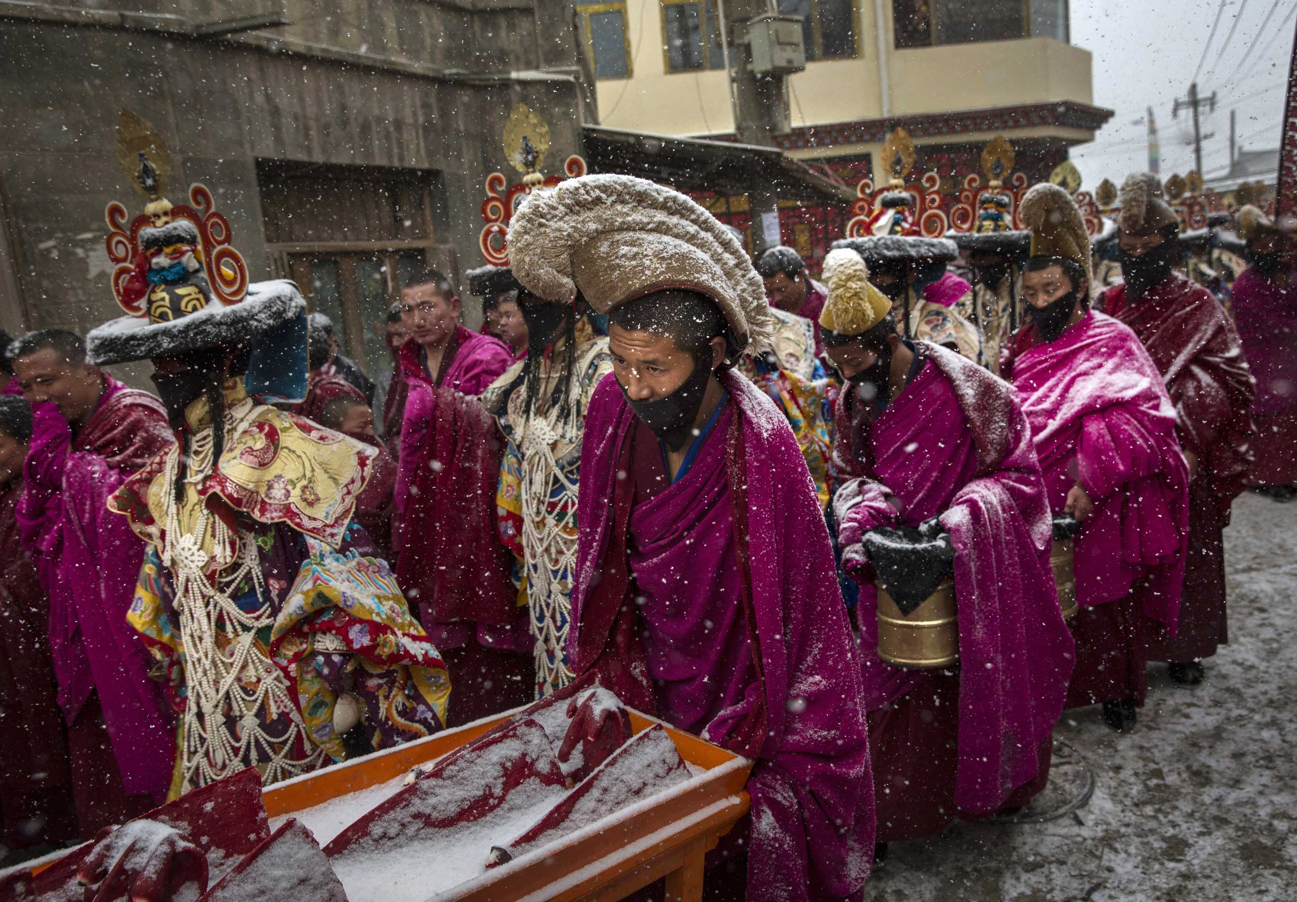 Tibetan Buddhist monks of the Gelug, or Yellow Hat order, are covered in snow as they take part in a procession during Monlam or the Great Prayer rituals on March 4, 2015 at the Labrang Monastery.