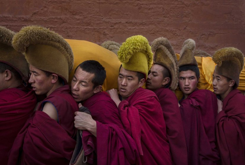 Tibetan Buddhist Monks of the Gelug, or Yellow Hat order, carry a large thangka of Buddha after showing it to worshippers during Monlam or the Great Prayer rituals on March 3, 2015 at the Labrang Monastery.