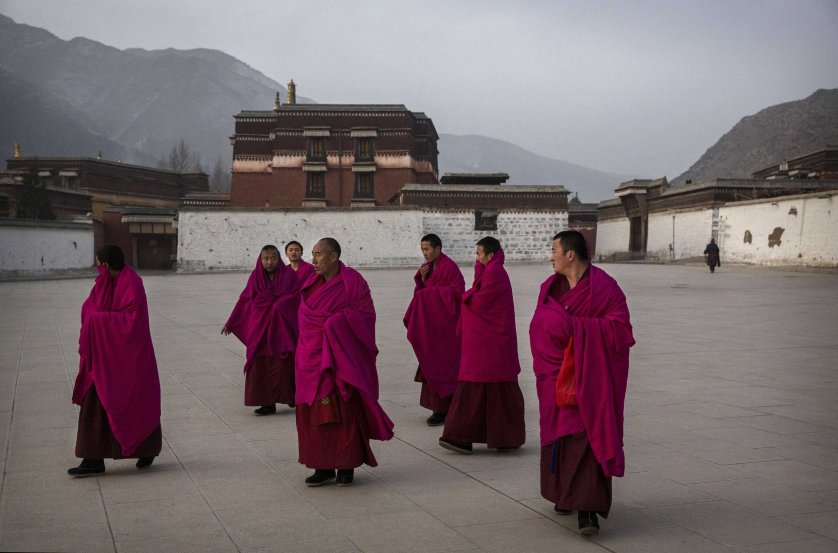 Tibetan Buddhist Monks of the Gelug, or Yellow Hat order, leave morning prayers during Monlam or the Great Prayer rituals on March 3, 2015 at the Labrang Monastery, Xiahe County, Amdo, Tibetan Autonomous Prefecture, Gansu Province, China.