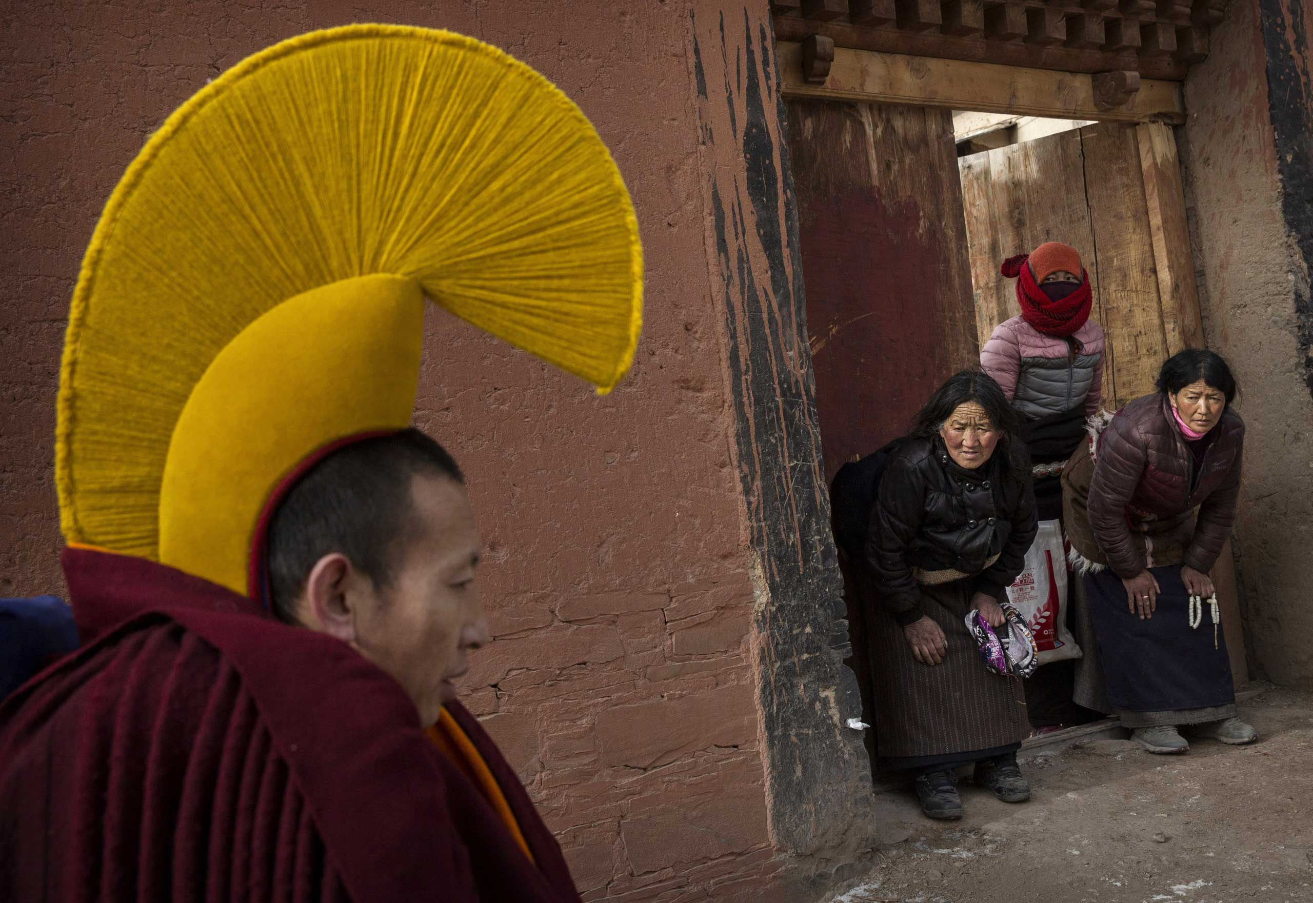 Devotees bow to a passing Tibetan Buddhist monk on his way to take part in a special prayer during Monlam or the Great Prayer rituals on March 5, 2015 at the Labrang Monastery.