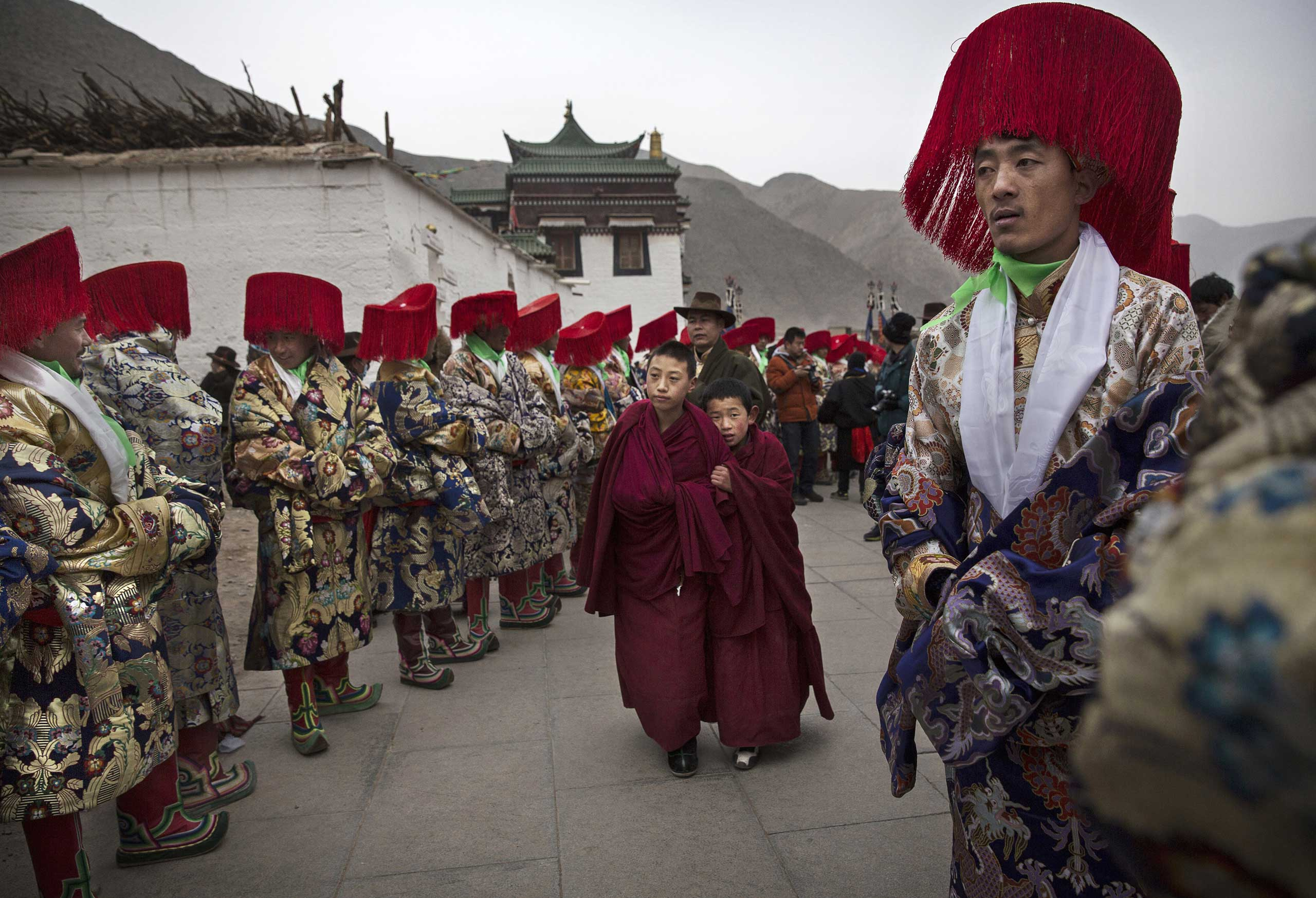 Two young Tibetan Buddhist monks of the Gelug, or Yellow Hat order, walk past men in traditional clothing before a procession during Monlam or the Great Prayer rituals on March 4, 2015 at the Labrang Monastery.
