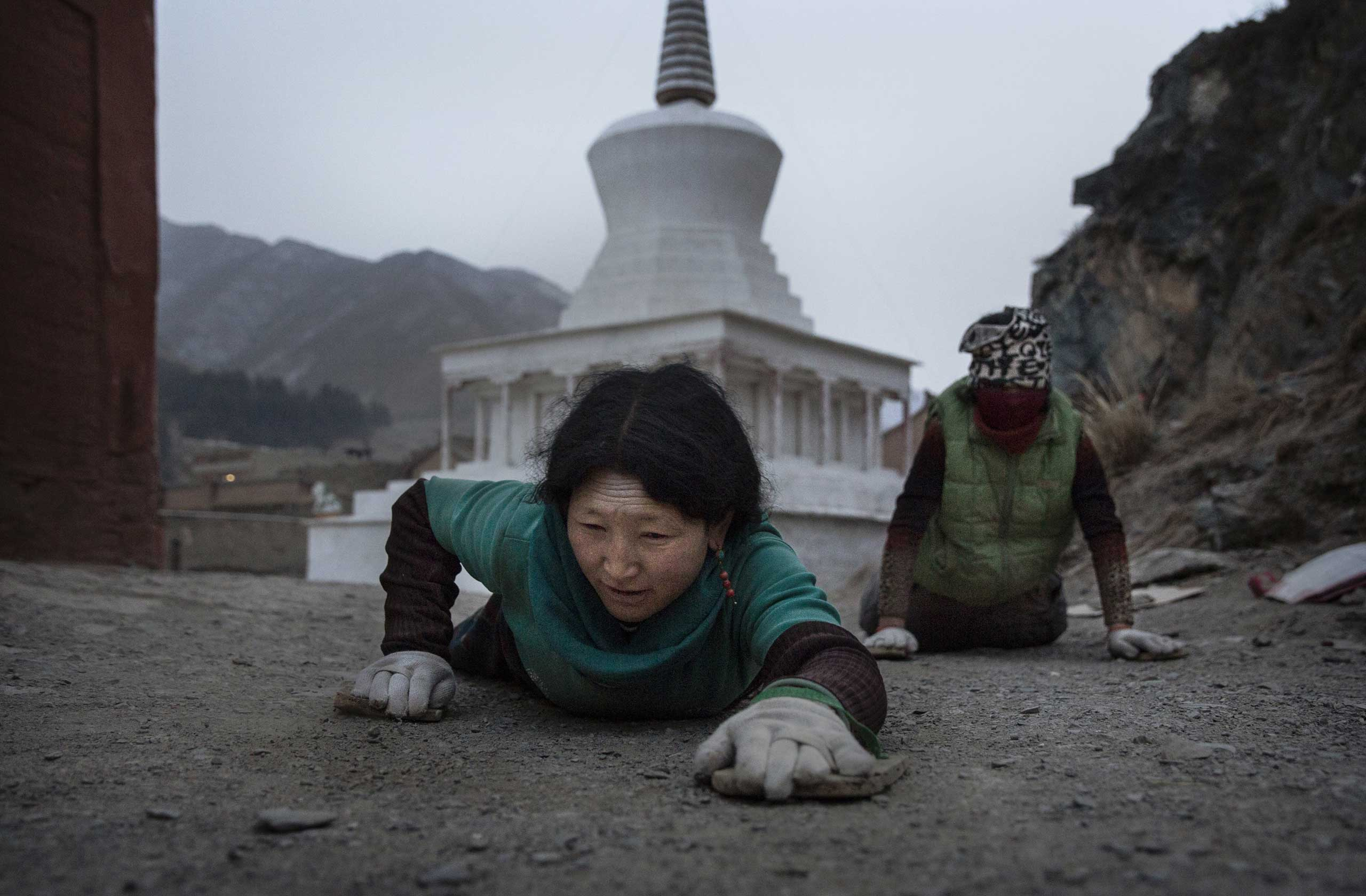A Tibetan Buddhist prostrates on the ground during a pilgrimage for Monlam or Great Prayer ritual on March 3, 2015 at the Labrang Monastery.
