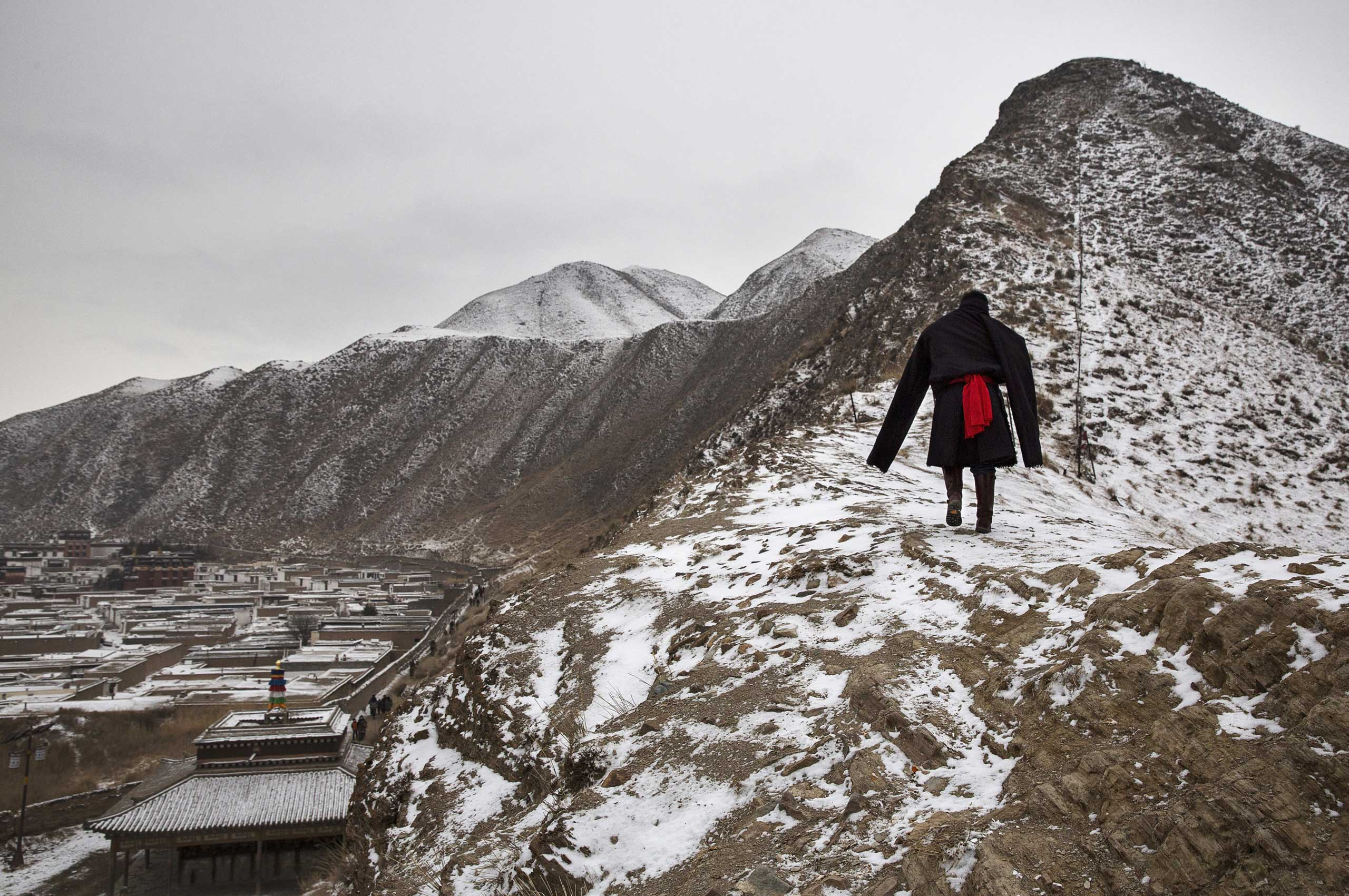 A Tibetan Buddhist man wears a traditional jacket as he walks on a hillside during  Monlam or the Great Prayer rituals on March 4, 2015 overlooking the Labrang Monastery.