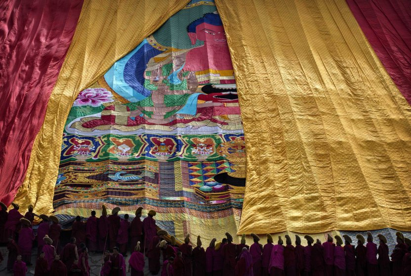 Tibetan Buddhist Monks of the Gelug, or Yellow Hat order, unveil a large thangka showing Buddha during Monlam or the Great Prayer rituals on March 3, 2015 at the Labrang Monastery.