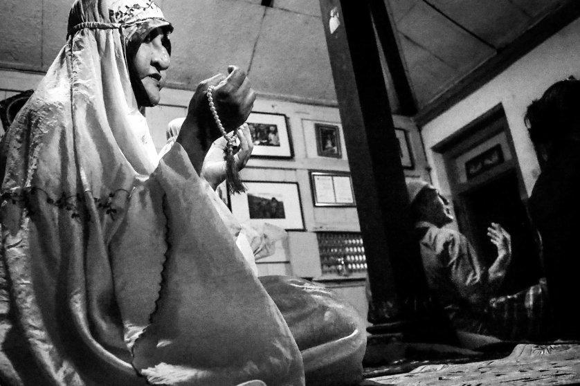 Shinta Ratri prays at the school, wearing mukena.