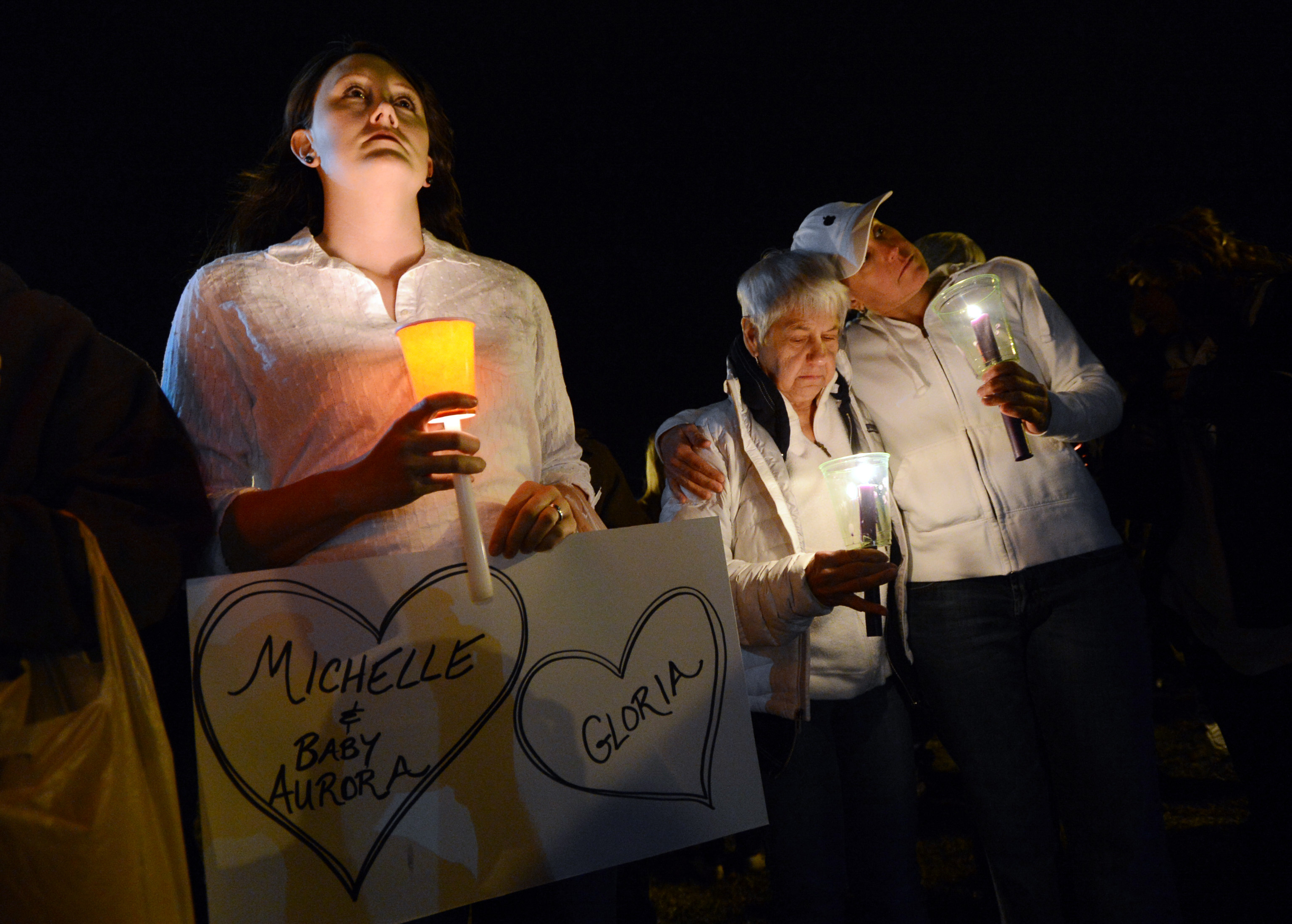 Cheryl Swanson, left, Elaine Derstine, and her daughter, Michelle Smith, are part of a moment of silence during the vigil.