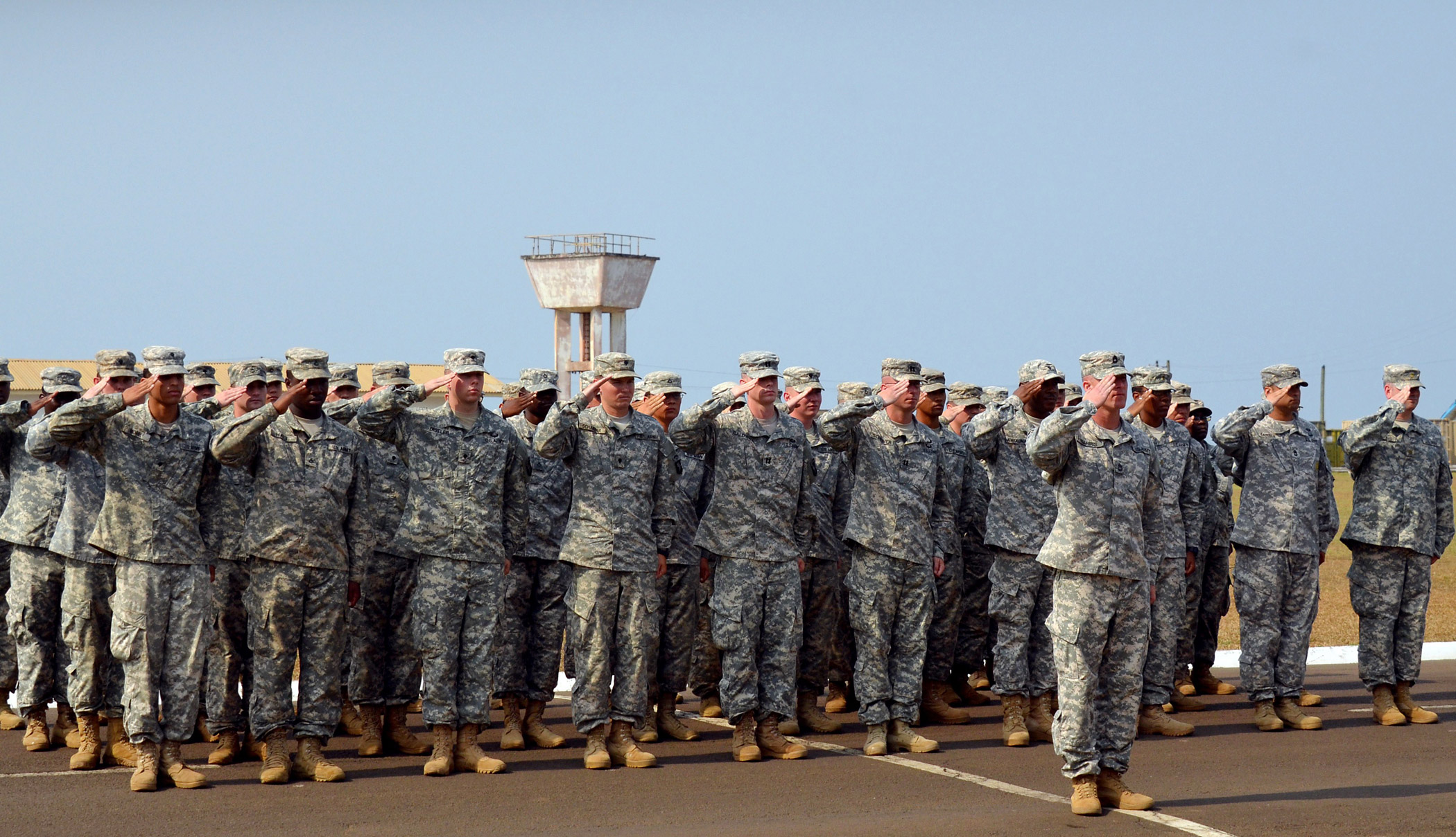 US soldiers of the 101st Airborne Division salute during the ceremonial folding and stowing of the flag at the Barclay Training Camp in Monrovia on Feb. 26, 2015, marking the end of the  Joint Forces Command United Assistance  mission.