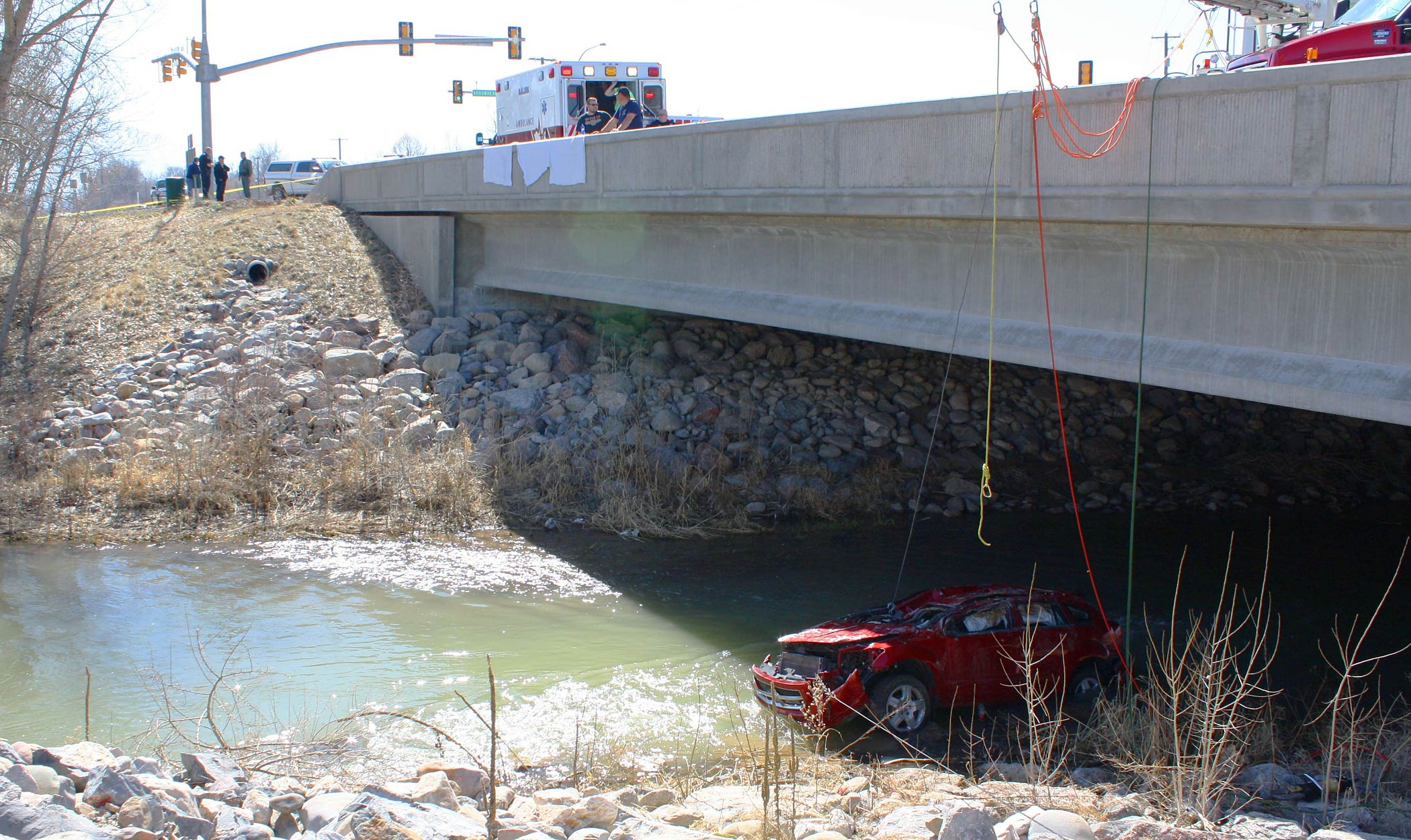 Emergency crews at the site where a vehicle plunged off a bridge into the Spanish fork River.
