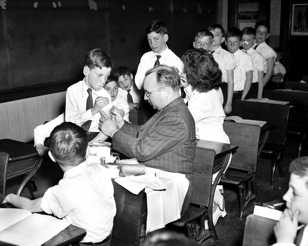 Joseph Burns, 8, grimaces as doctor vaccinates him at St. Joan of Arc Parochial School in Jackson Heights, Queens, New York, in 1947