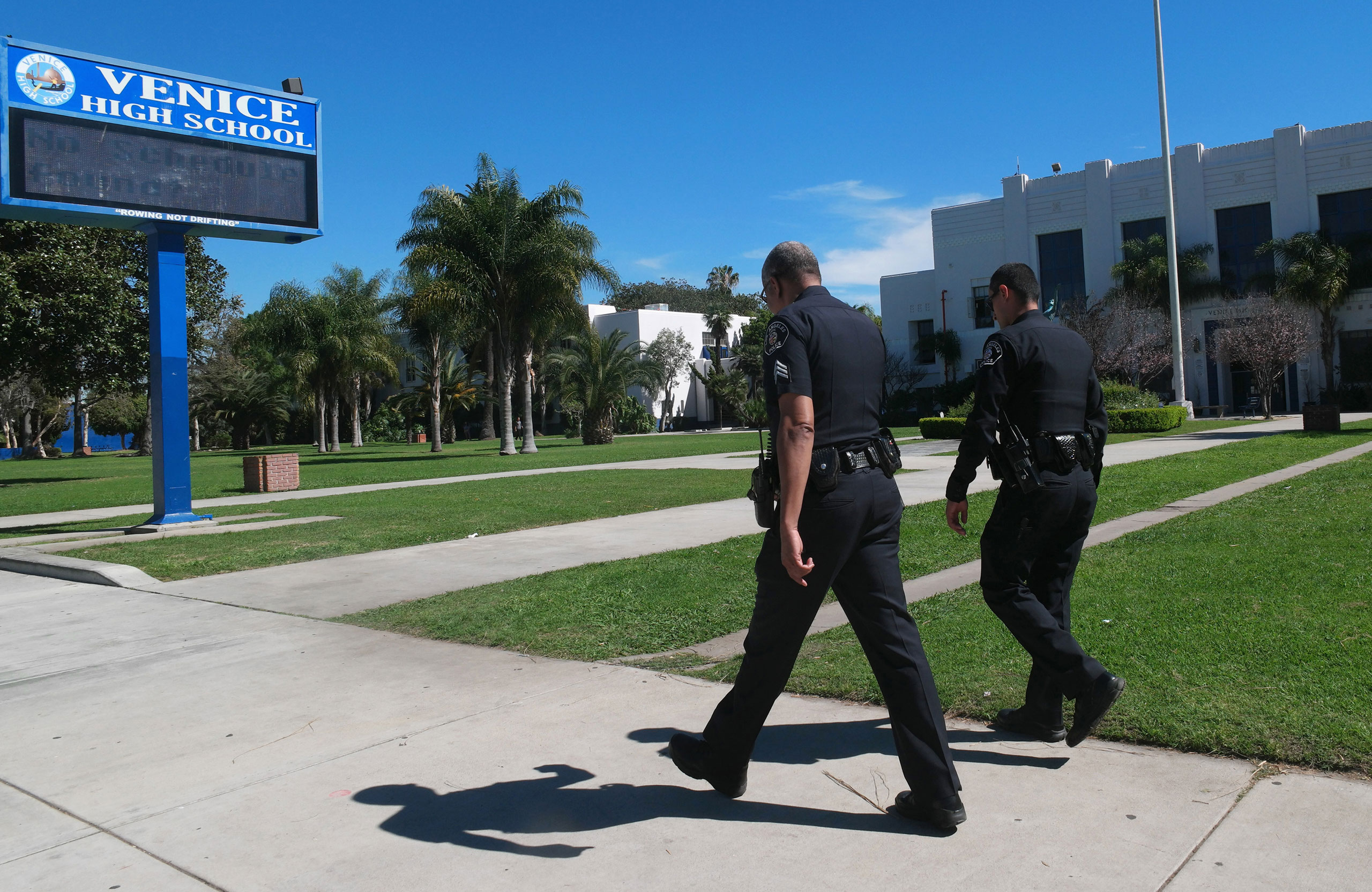 Police officers walk in front of Venice High School, where they are investigating allegations of sexual assaults centered on students, in Los Angeles, March 13, 2015.