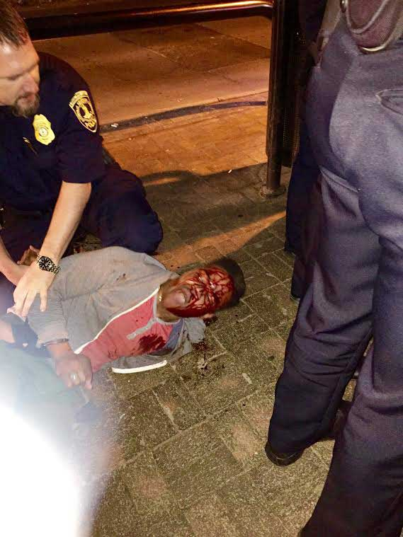 In this photo provided by Bryan Beaubrun, Martese Johnson is held down by an officer Wednesday, March 18, 2015, in Charlottesville, Va.