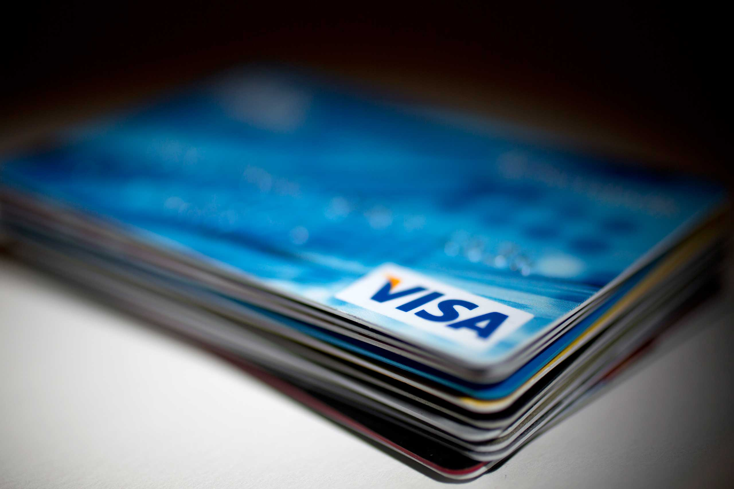 A Visa Inc. credit card sits on top of credit and debit cards arranged for a photograph in Washington on Jan. 29, 2014.