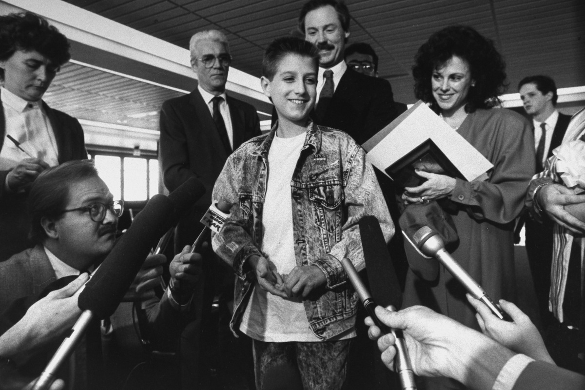 Ryan White, 16, a hemophiliac who contracted AIDS, surrounded by mikes held out by reporters on April 21, 1988