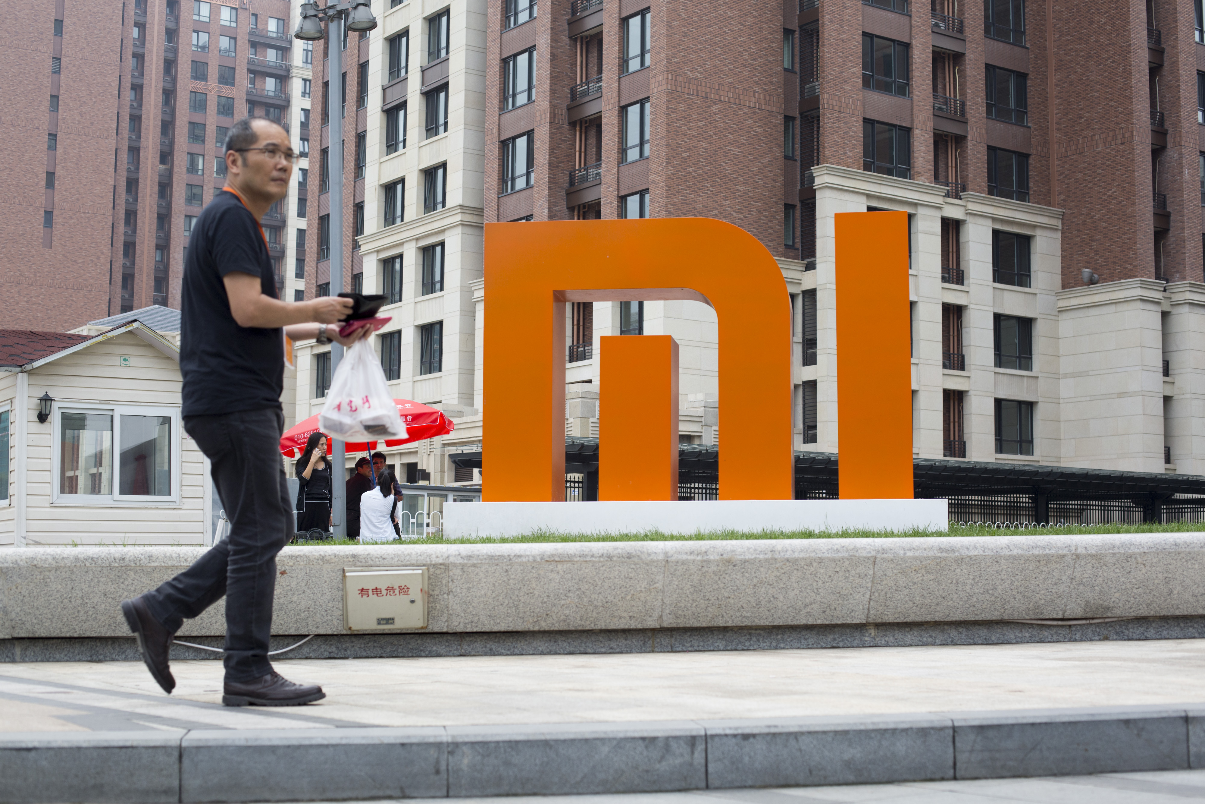 A man walks past a Xiaomi Corp. logo displayed outside the company's headquarters in Beijing, China, on Sept. 12, 2014.