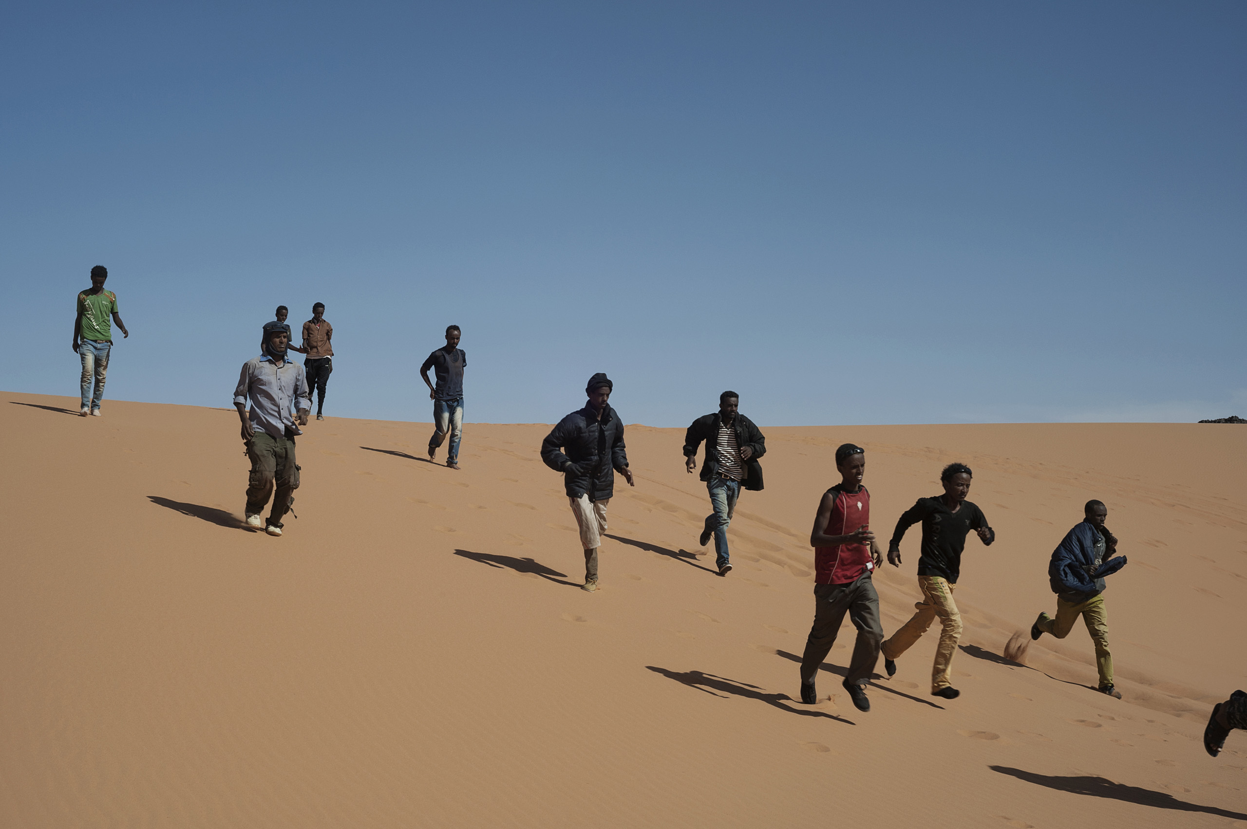 Refugees run to reach their transport to continue their journey in Libya, near the border with Egypt, May 18, 2014.