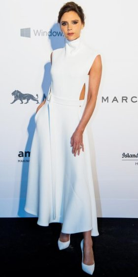 MARCH 14, 2015 At the amfAR Hong Kong gala, the star struck minimalism-chic in a white high-neck sleeveless dress of her own design with a full, sweeping skirt and cut-outs at the bodice. White pumps completed her monochromatic palette.