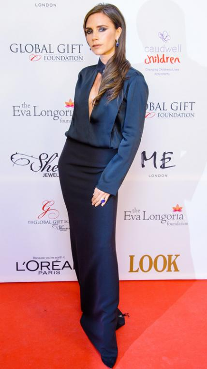 NOVEMBER 19, 2013 Beckham hit the London Global Gift Gala in pieces from her eponymous line, which included a dark long-sleeve blouse and a black maxi. She added a pop of color and sparkle with sapphire and diamond Harry Winston drop earrings.