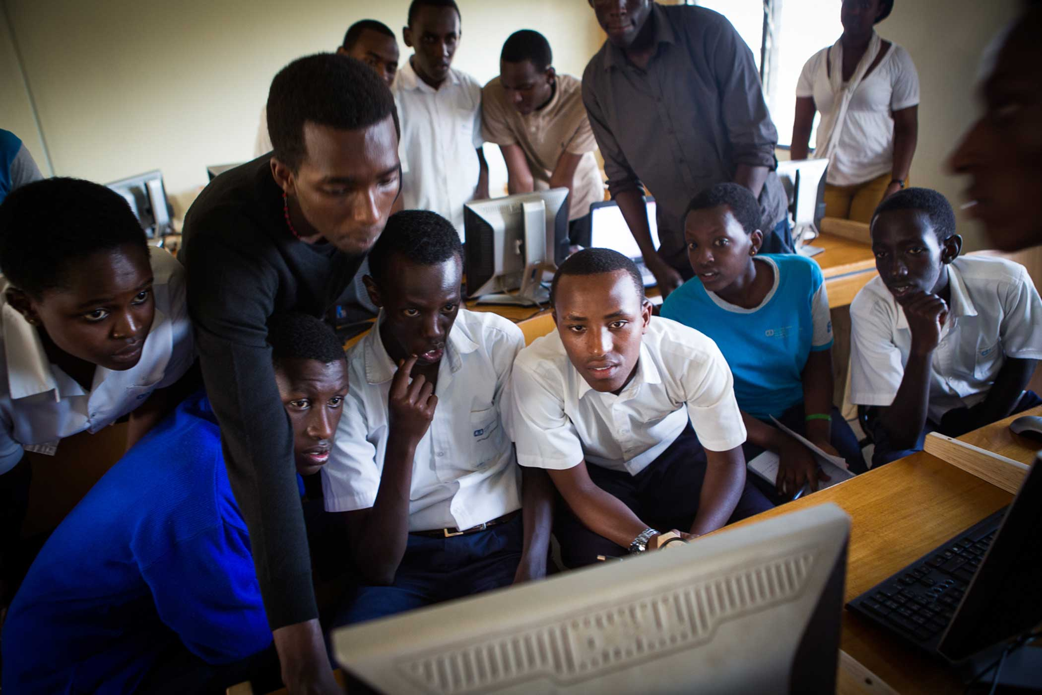 Coding fellows gather around a computer to learn HTML at an after school program run by HeHe Labs at S.O.S. Technical High School.