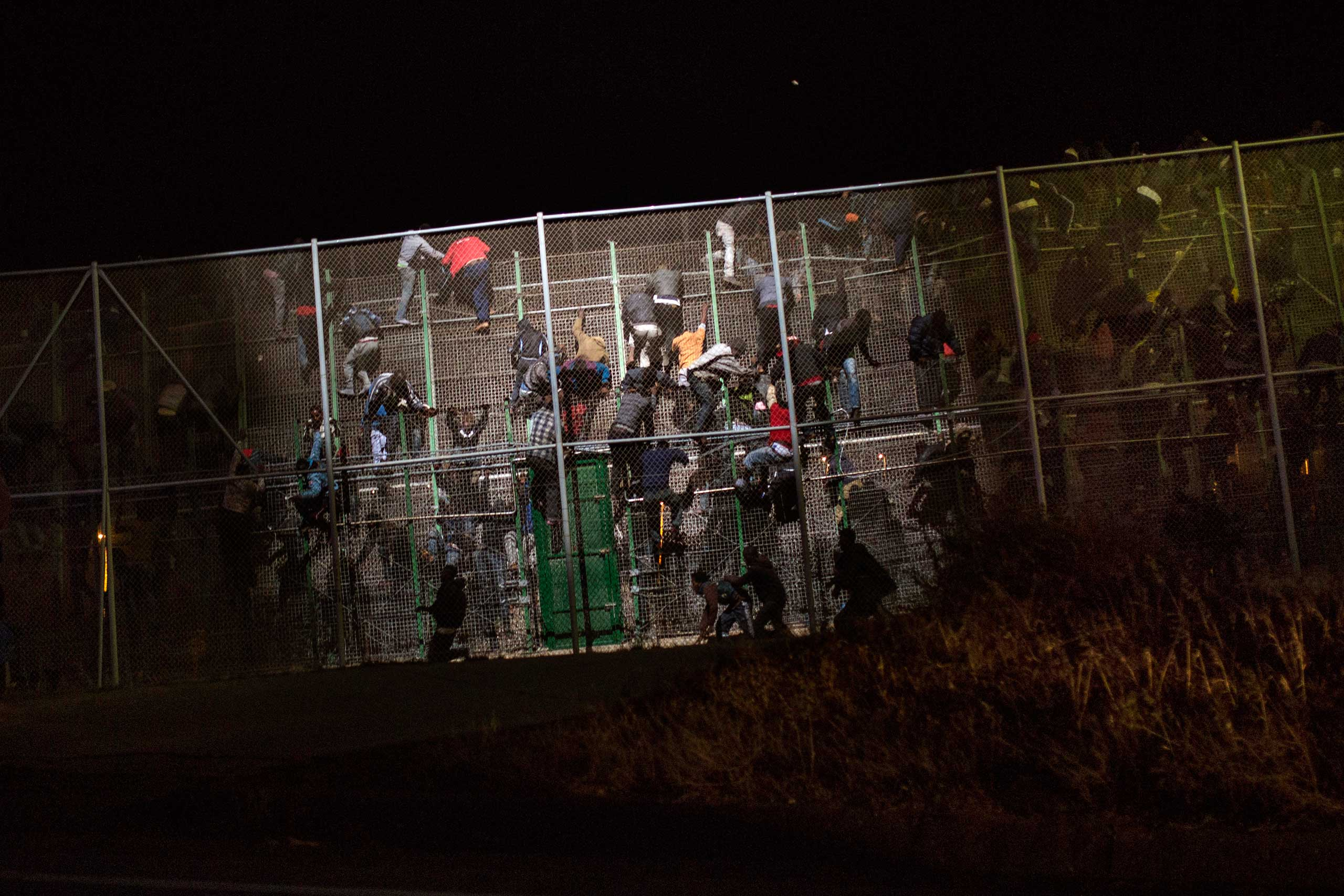 Sub-Saharan migrants scale a metallic fence that divides Morocco and the Spanish enclave of Melilla, May 28, 2014.