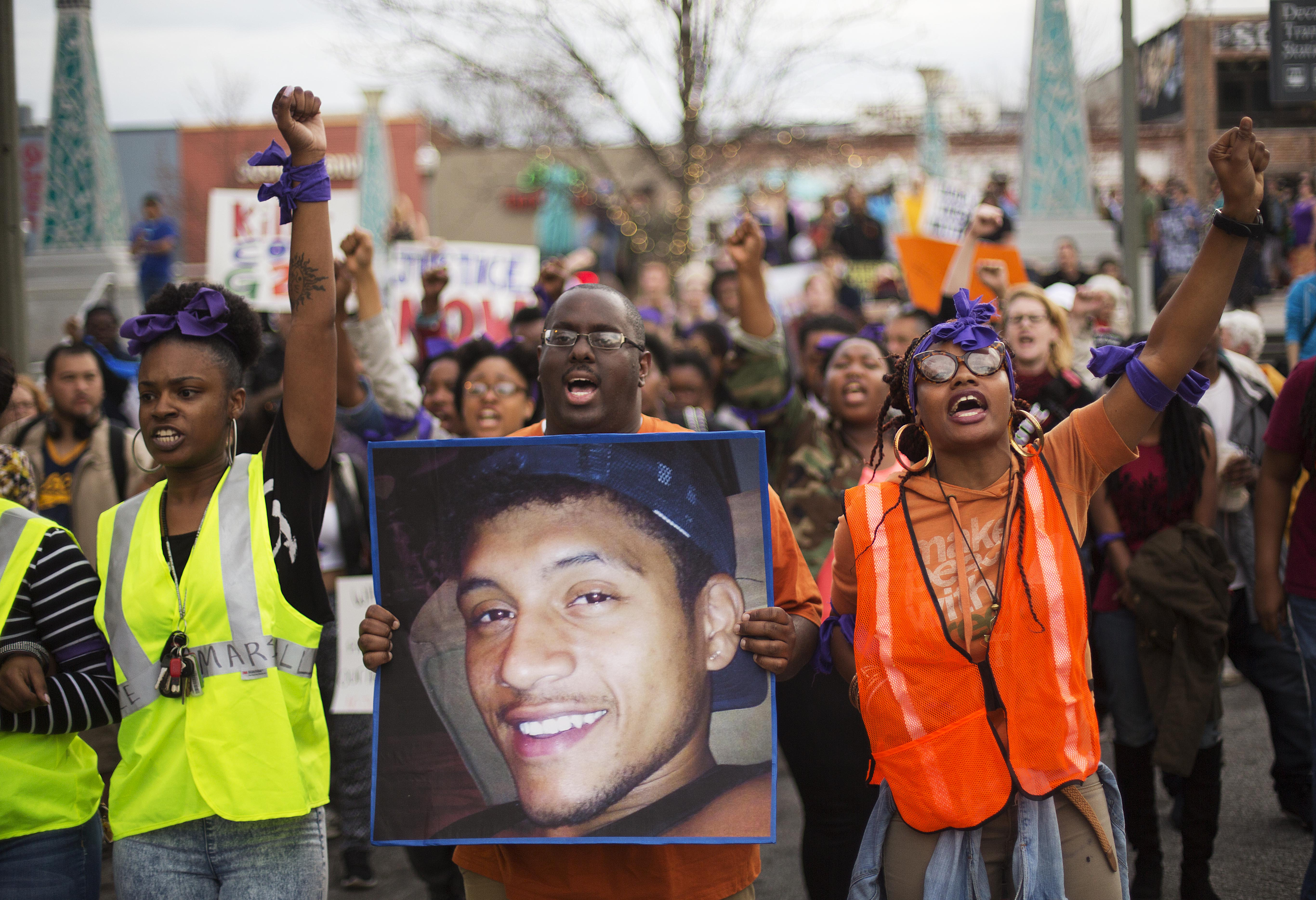 Protesters carry a photo of Anthony Hill while marching through the street demonstrating Hill's shooting death by a police officer in Decatur, Ga. on March 11, 2015.