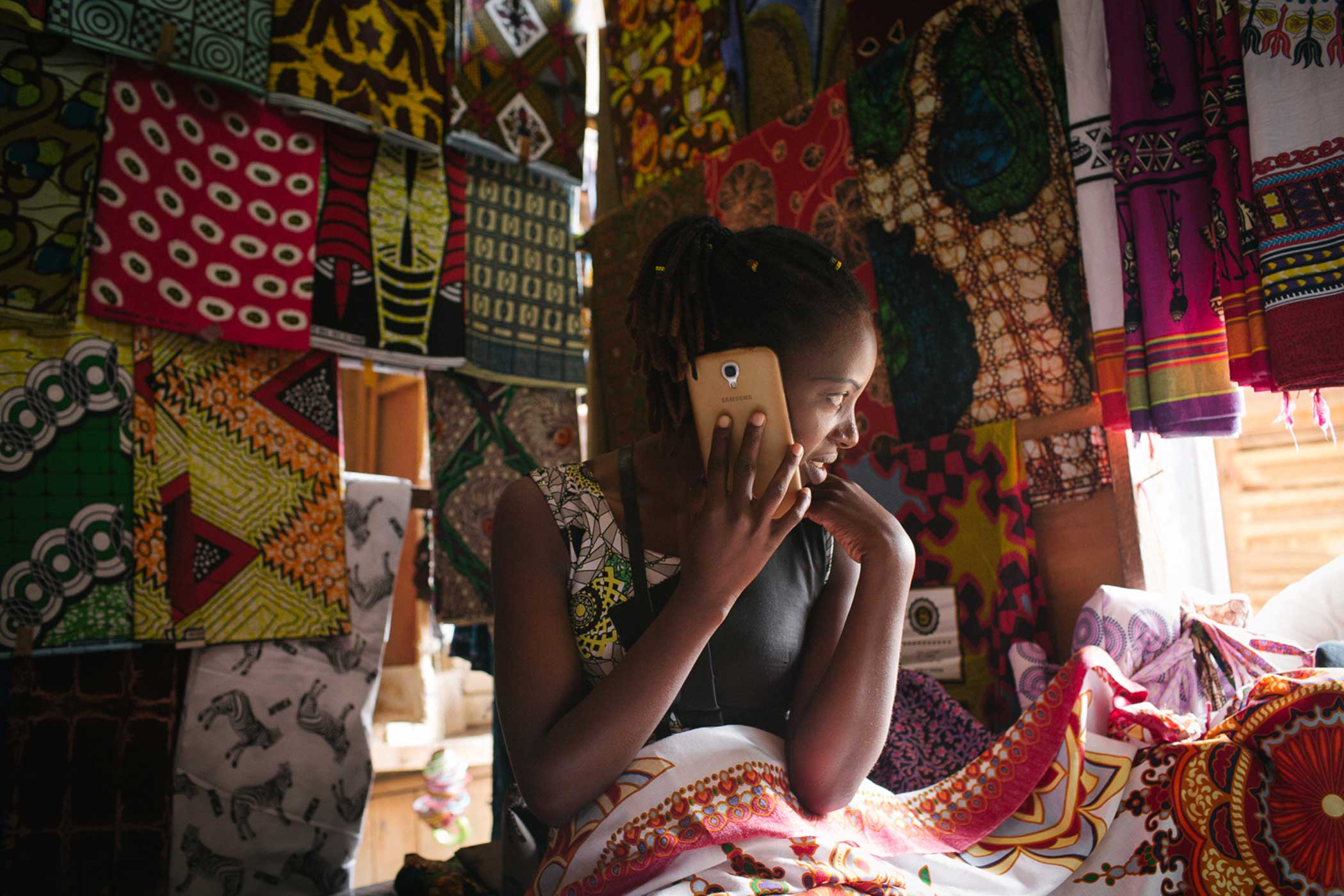Josephine Niyigena, 25, chats with a friend on her cell phone while she sells fabric at Kimironko market in Kigali. The cellular network covers nearly 98% of the population.