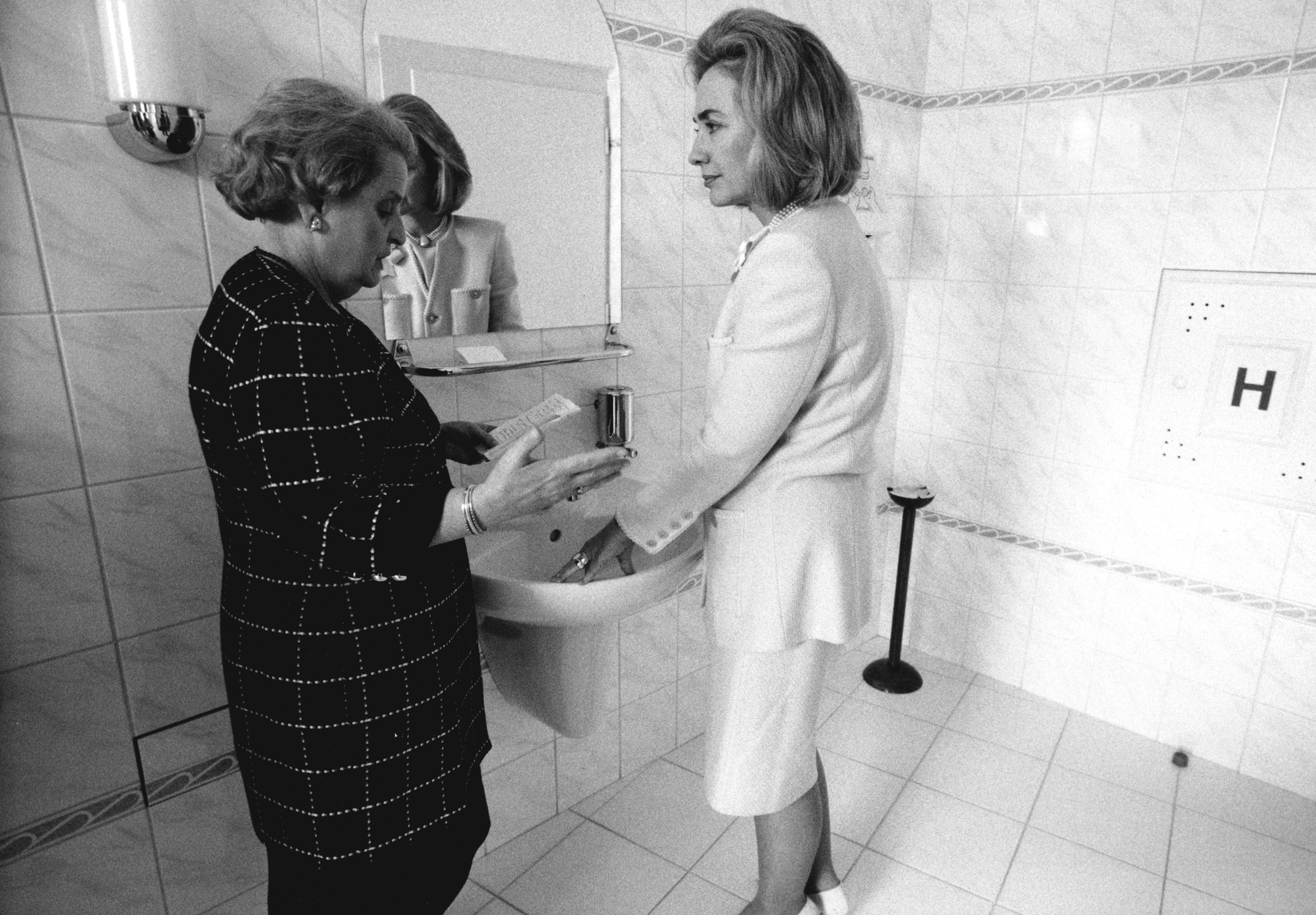 Secretary of state Madeleine Albright briefs First Lady Hillary Clinton in a ladies room during a trip to Prague, 1997.