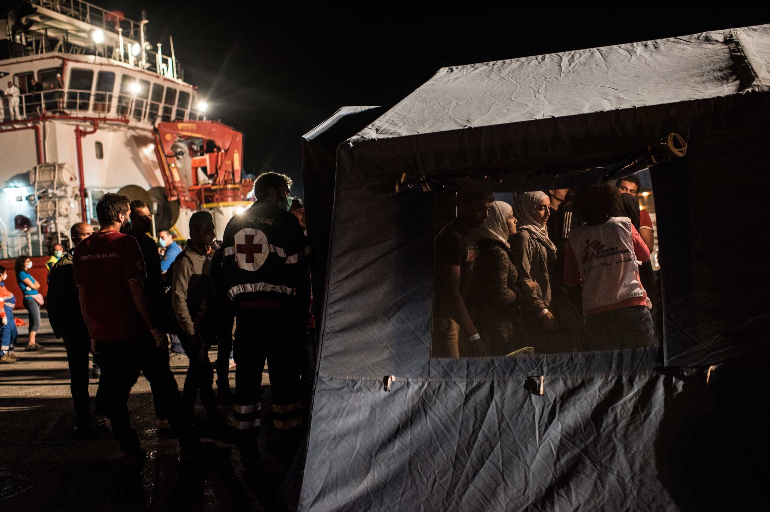 Roughly 250 refugees from Egypt and Syria, among other countries, are checked by Doctors Without Borders as they disembark from an Italian ship, after being intercepted and rescued at sea en route to Italy from Egypt to the port in Pozzallo, Sicily, Italy, in Sept. 2014.