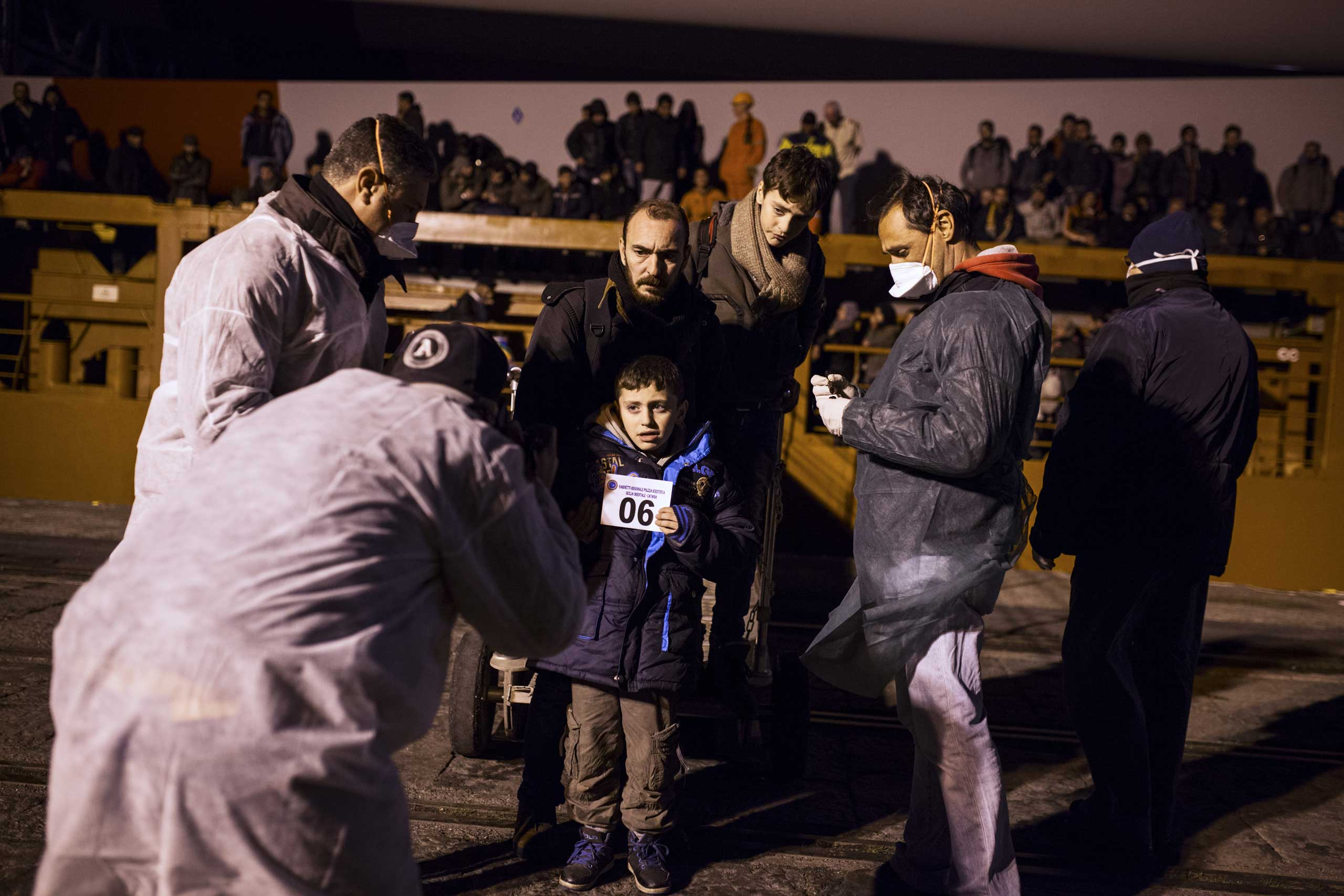 A family of Syrian refugees holds its identification. Nearly 300 Syrians landed in the port of Catania, Dec. 6, 2014.