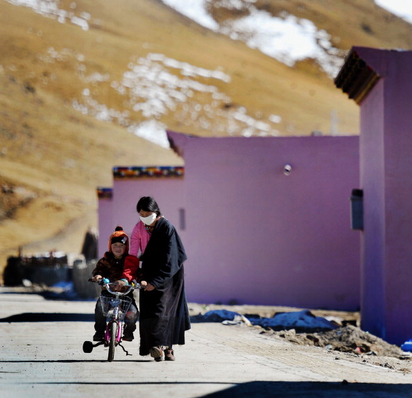 A Tiben woman teaches her son to ride a bike beside their new house in Yushu, northwest China's Qinghai province on Nov. 13, 2011