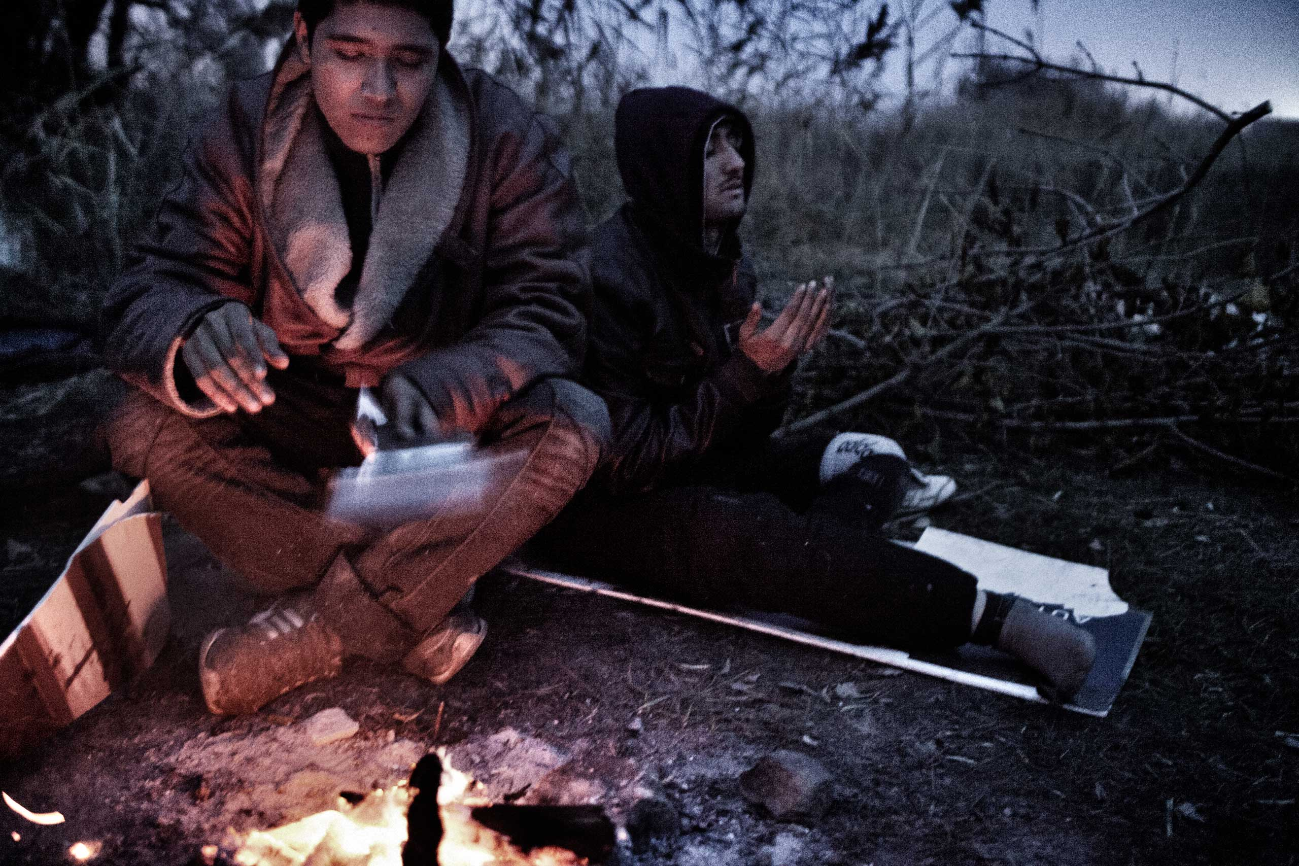 Afghan refugees, Kabir and Zaher, sit by a fire in Subotica, Serbia, Nov. 10, 2012. Zaher, who lost his left leg below the knees, made it to Serbia on crutches. Zaher says he is 16 and Kabir 15. The two were traveling together from Greece. The men lived outdoors in Subotica, waiting for smugglers to give the green light to continue their journey.