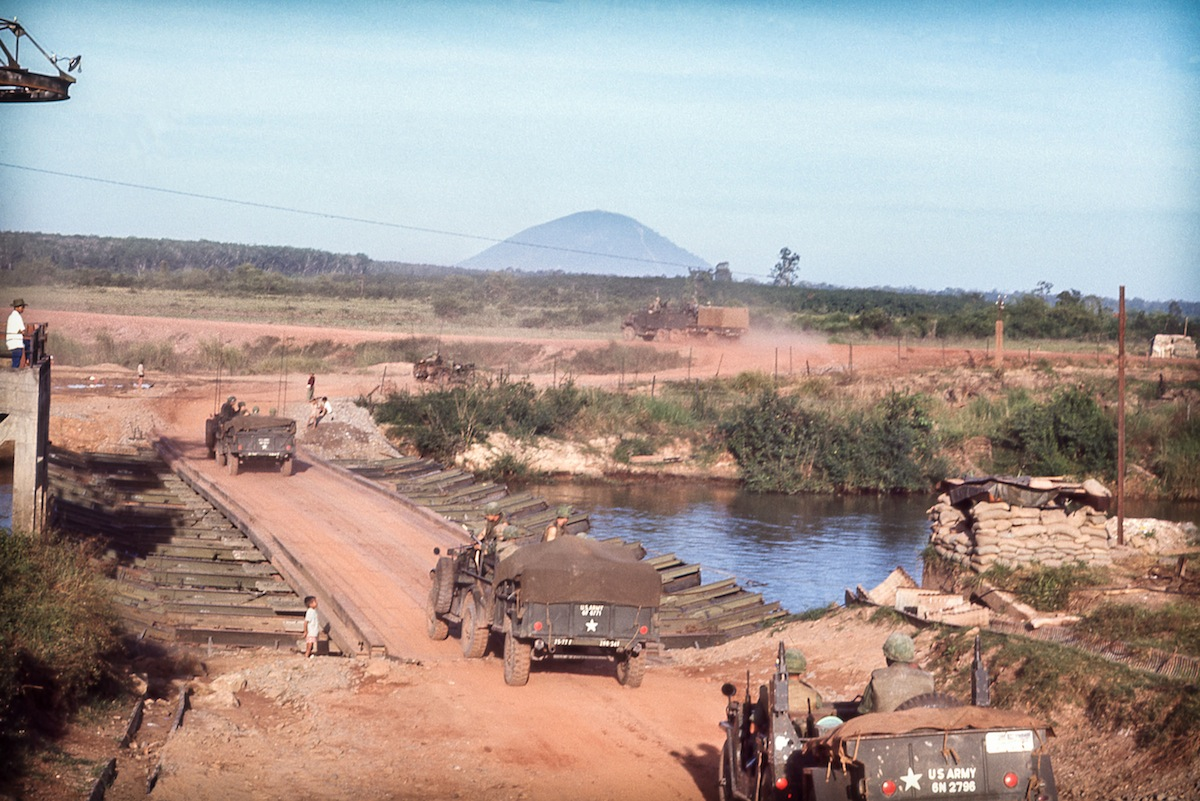 "Núi Bà Đen, 1967: ""The Black Virgin Mountain looms in the background as our convoy of the 2nd Battalion, 77th Field Artillery Regiment, 4th Infantry Division crosses the Saigon River heading North West to Loc Ninh to support our infantry units from an artillery Fire Support Base."""