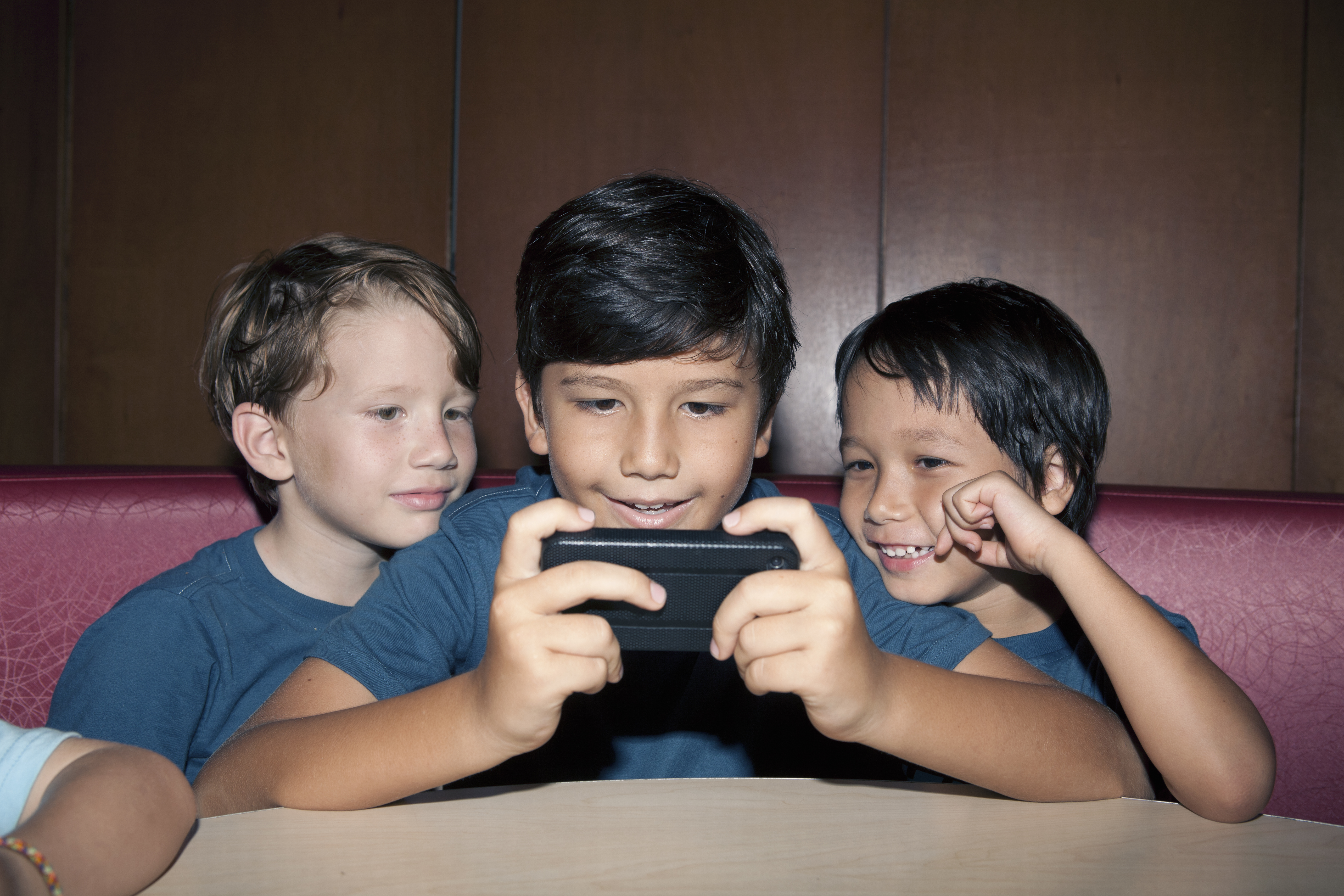 Young boys playing games with smartphone