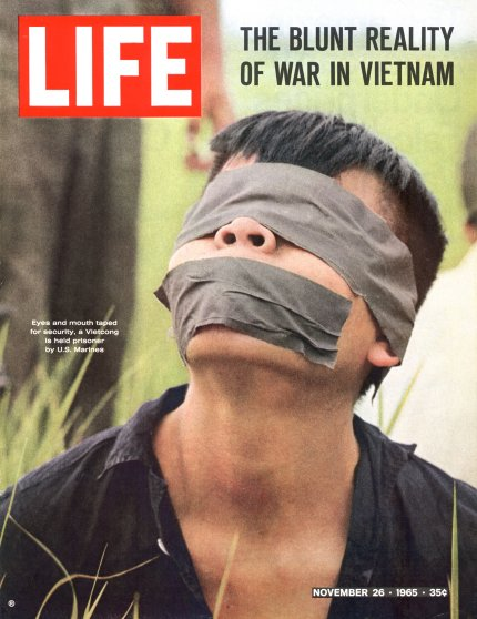 Eyes and mouth taped for security, a Vietcong is held prisoner by U.S. Marines.