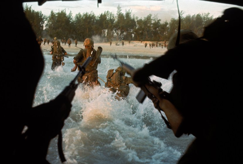 Swarming out of Amtrak into surf, Leathernecks of the Seventh Marines storm ashore under cover of overhead fire. The beach is mined and snipper fire is coming from the tree line.
