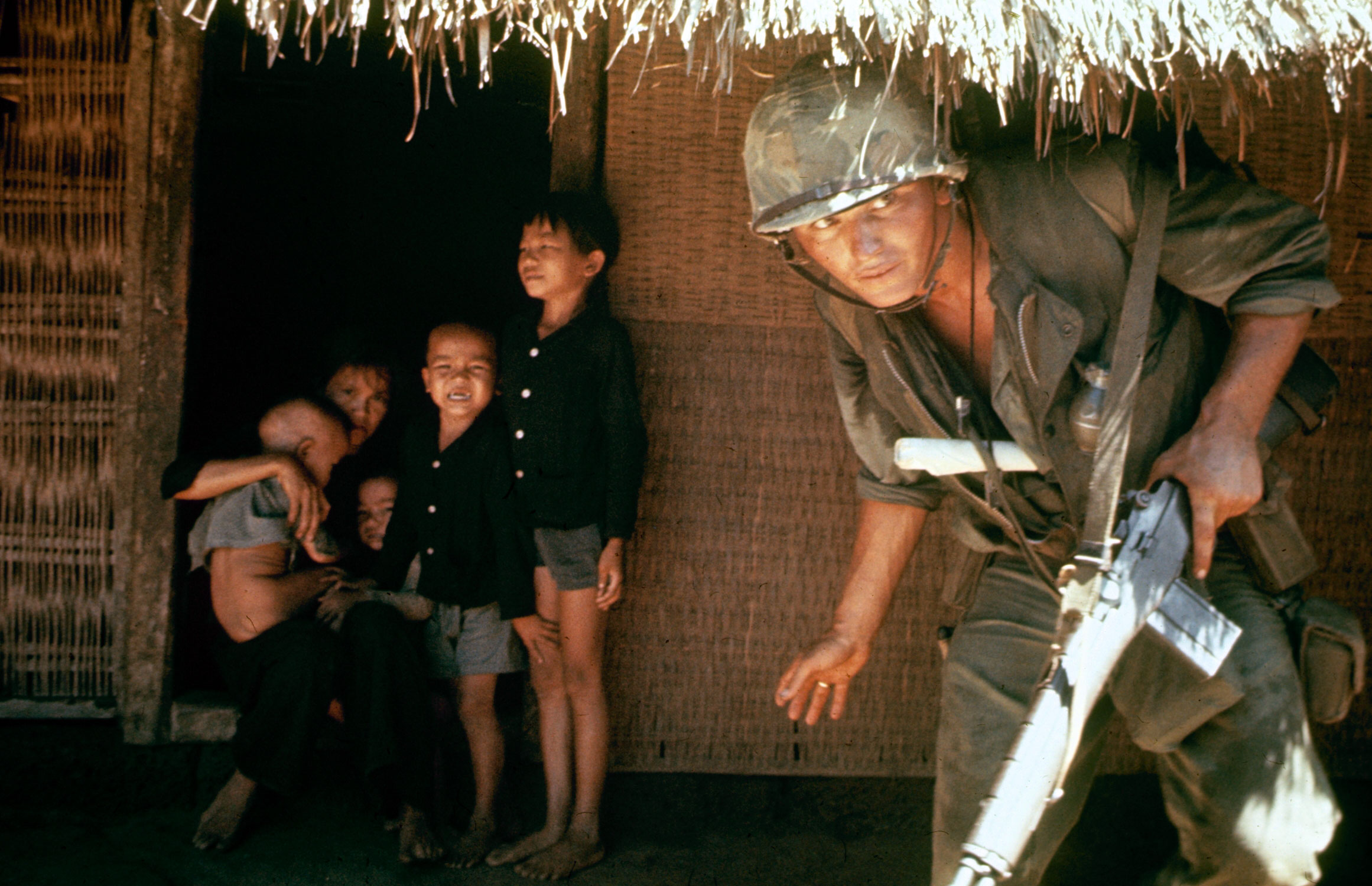 Caption from LIFE. Within the village children shrink from a scout hunting the V.C. who strike from tunnels under huts.
