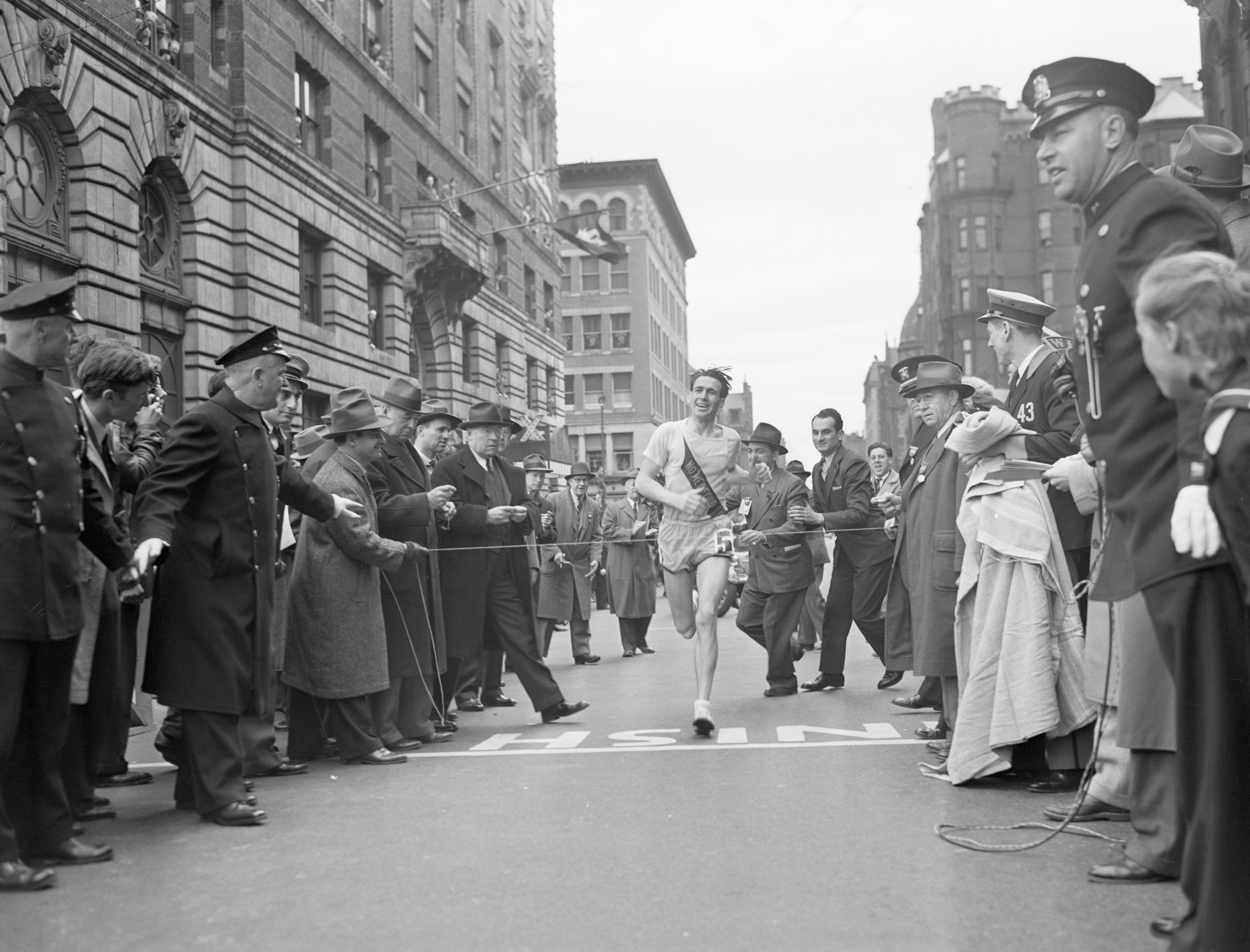 Joe Smith. 36 year old Medford, Mass., milkman, crosses the final line to win the 46th renewal of the Boston A. A. Marathon, setting a new world mark of 2 hours 26 minutes 51 1/5 seconds, in 1941.