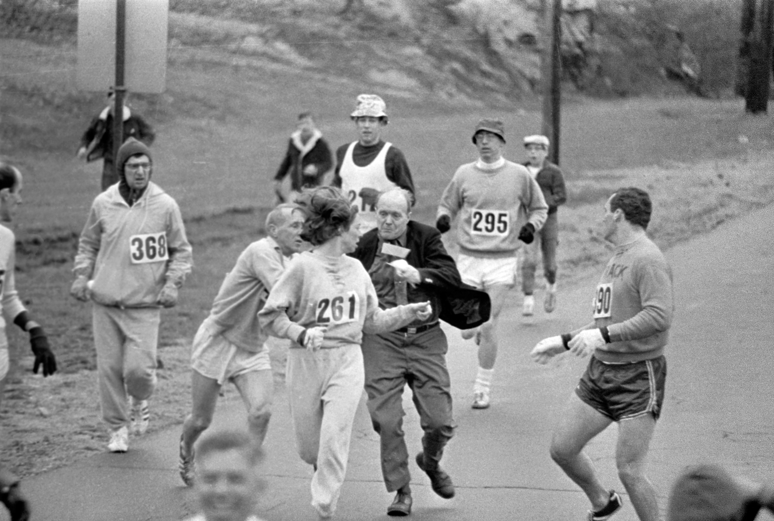 The rule that no women shall run in the Boston Athletic Association (BAA) Marathon is being put to a very real test in this photo. Trainer Jack Semple (in street clothes) enters the field of runners to try to pull Kathy Switzer (261) out of the race. Male runners move in to form protective curtain around the female track hopeful, until the protesting trainer is finally wedged out of the race, and Switzer is allowed to finish the marathon.