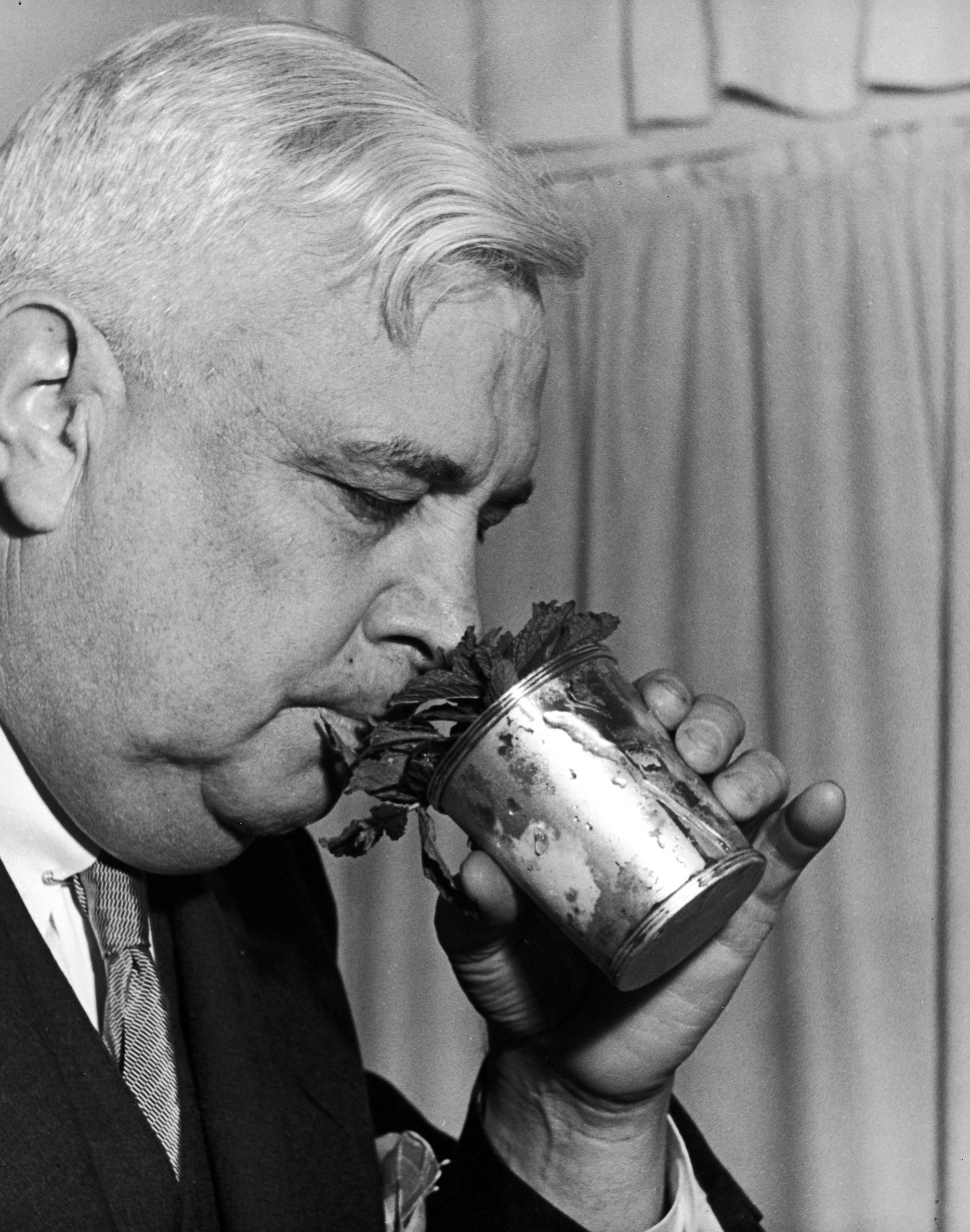 Caption from LIFE. A perfect mint julep expression is here displayed by Jonathan Van Dyke Norman, who critically sniffs the aroma of mint and Bourbon as he holds a silver mug somewhat defrosted by affectionate handling.