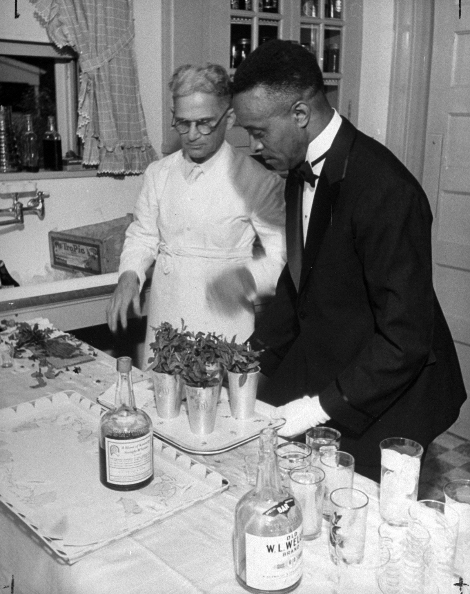 Caption from LIFE. The Van winkle kitchen was a pleasant scene of hospitable preparation as trayful after trayful of silver-mugged mint juleps were sent to the appreciative Derby Week guests.