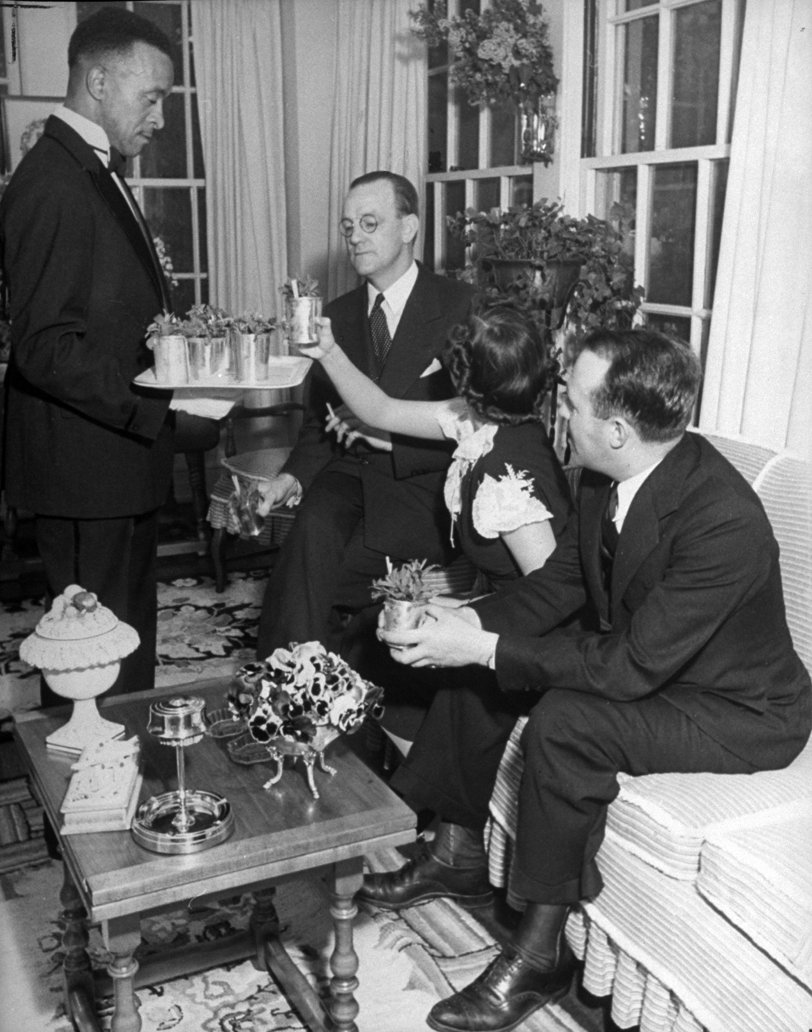 Caption from LIFE. Congenial celebrants at the Van Winkle mint julep party included, from left to right, T. V. Hartnett, tobacco bigwig; Mary Van Winkle, the host's daughter; Richard Dewey.