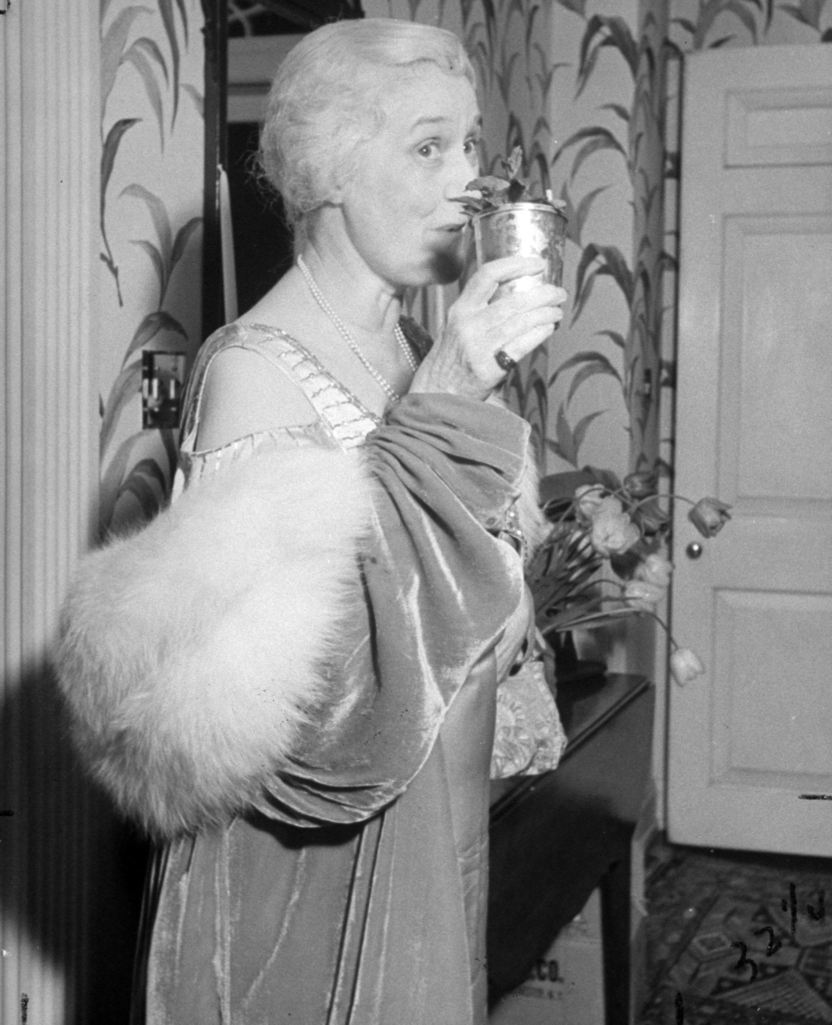 Caption from LIFE. Mint julep drinker Mrs. Eugene Walker demonstrates how a Louisville belle manages to achieve maturity gracefully and happily.
