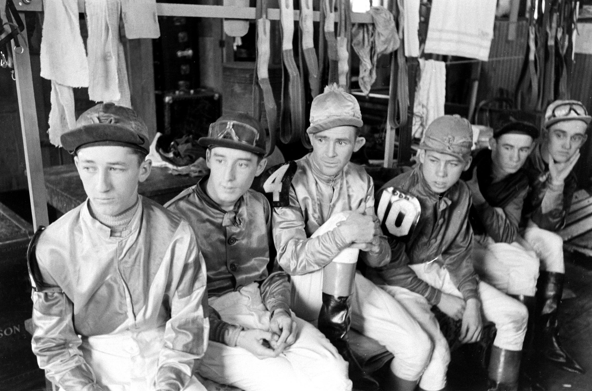 Caption from LIFE. Churchill Downs jockeys in their quarters, include several who rode in the Kentucky Derby. At lower left is Hubert Leblanc who rode Miss Mary Hirsh's No Sir. Next to him is Hilton Dabson, who rode William Shea's and Miss E. G. Rand's Merry Maker. Fourth from left, with the number 10 on his sleeve is Basil James, who rode J. W. Parrish's Dellor.